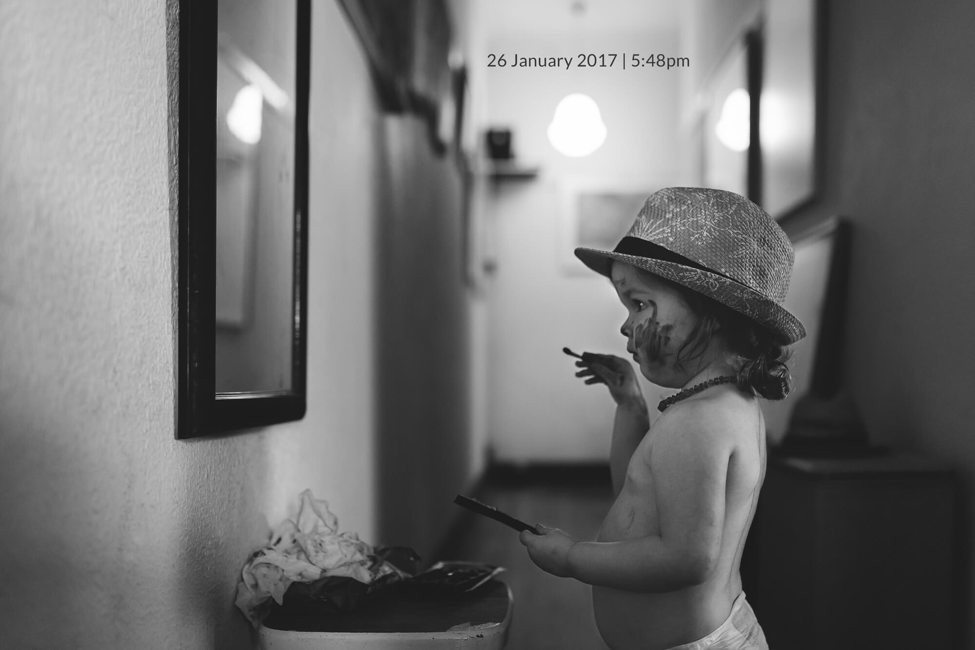 Melbourne family photography. Portrait of a young girl in a hat looking at herself in the mirror.
