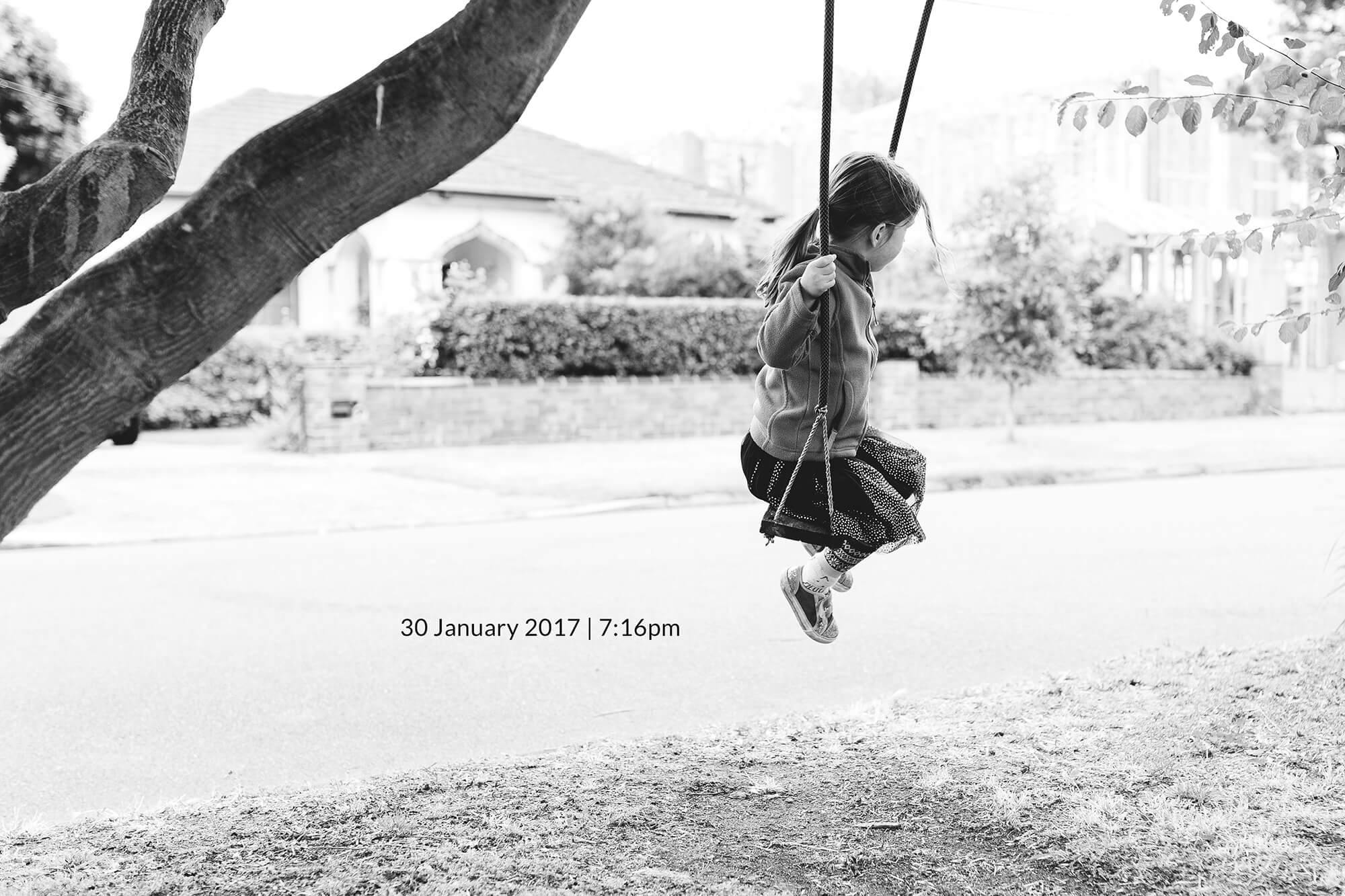 Melbourne lifestyle family photography. Photo in black and white of a young girl on a swing.