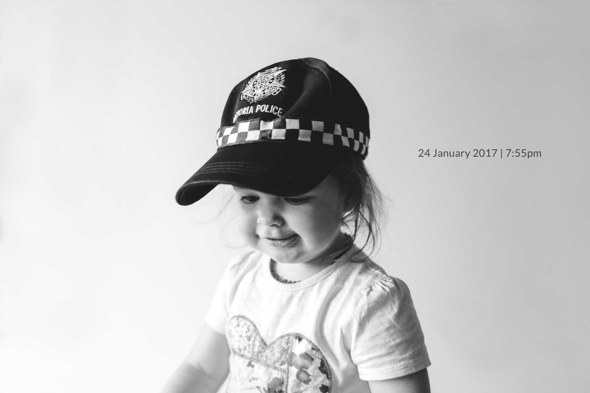 Family lifestyle photography in Melbourne. Portrait of a toddler wearing a police cap.