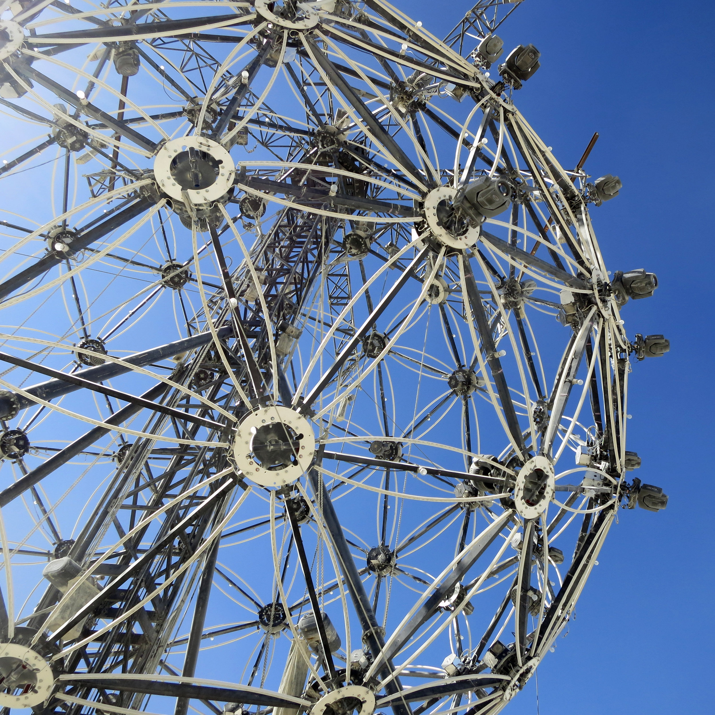 A gigantic, mechanical latticework orb contrasts the desert sky. The Ball by L'Enclave, 2015