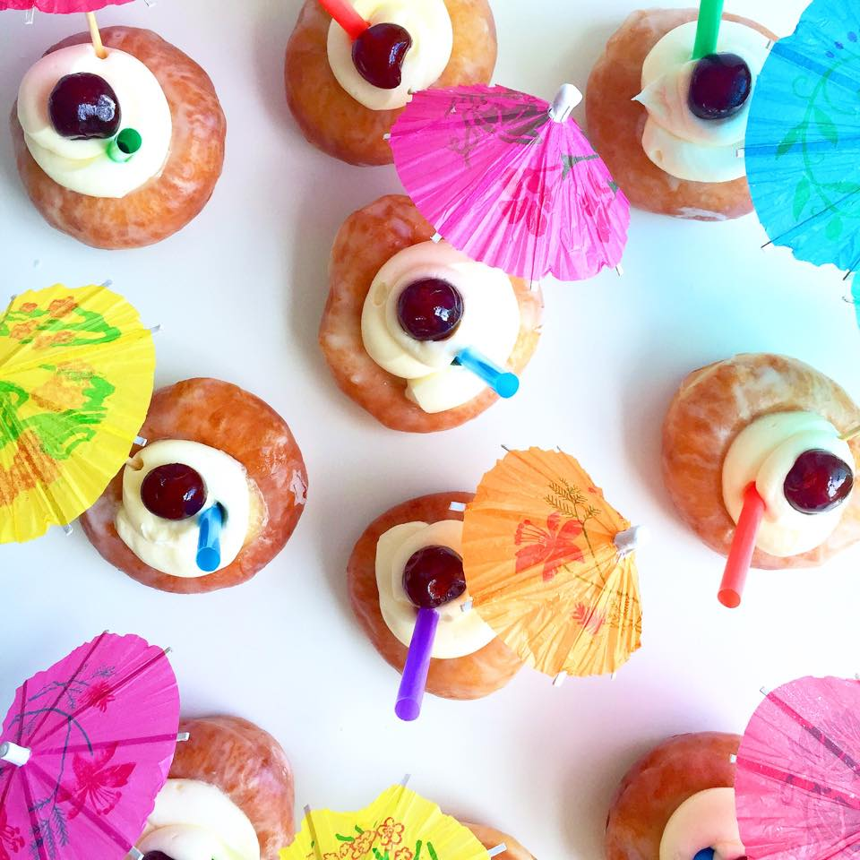 Mini pina colada donuts: coconut buttercream with a straw to suck out the pineapple curd, topped with a mini umbrella