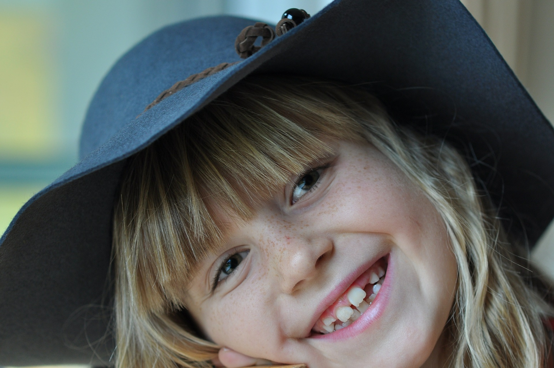 Laughing girl with a blue hat.