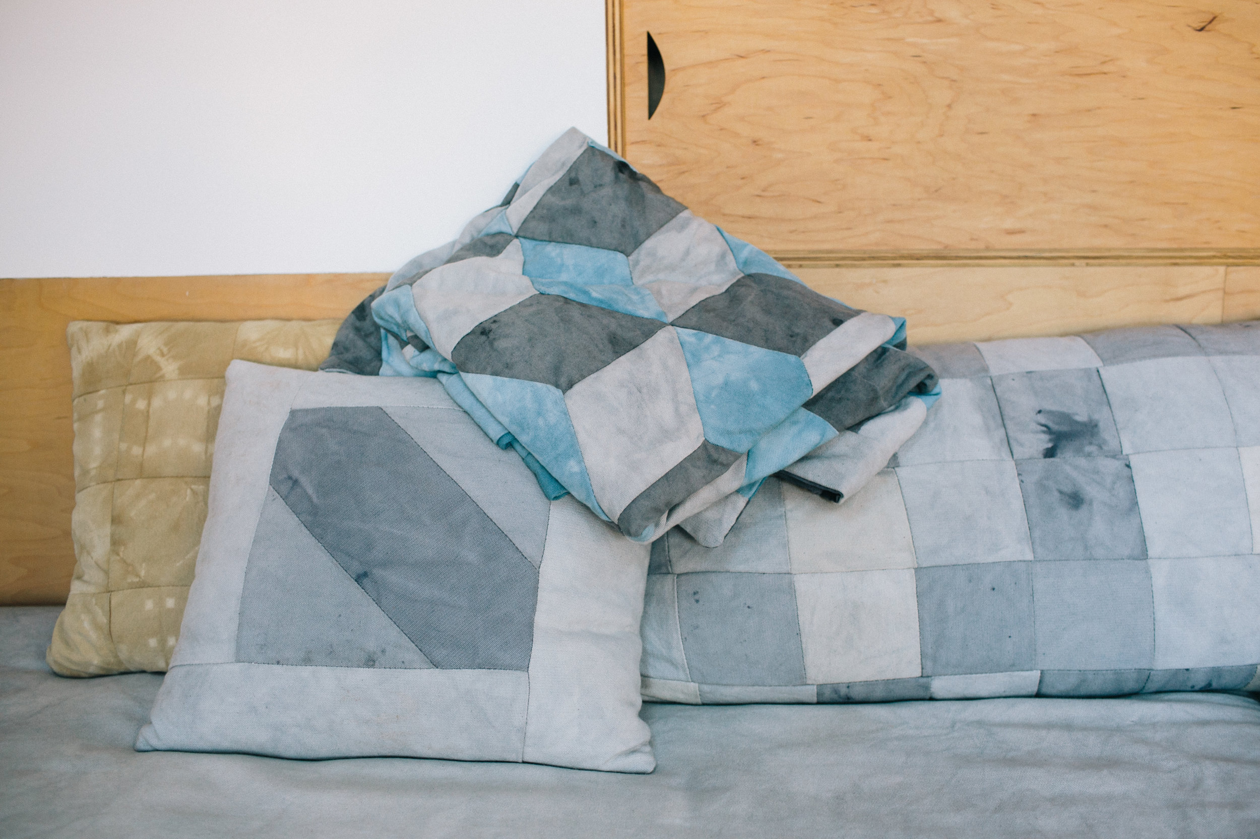 Pillow (back left)- Pine Bark Dye on Cotton Canvas Pillow (center and back right) - Oak Galls & Iron Dye on Canvas Tumbling Blocks Quilt - (on top of pillows) - Oak Galls & Iron and Indigo Dye on Canvas