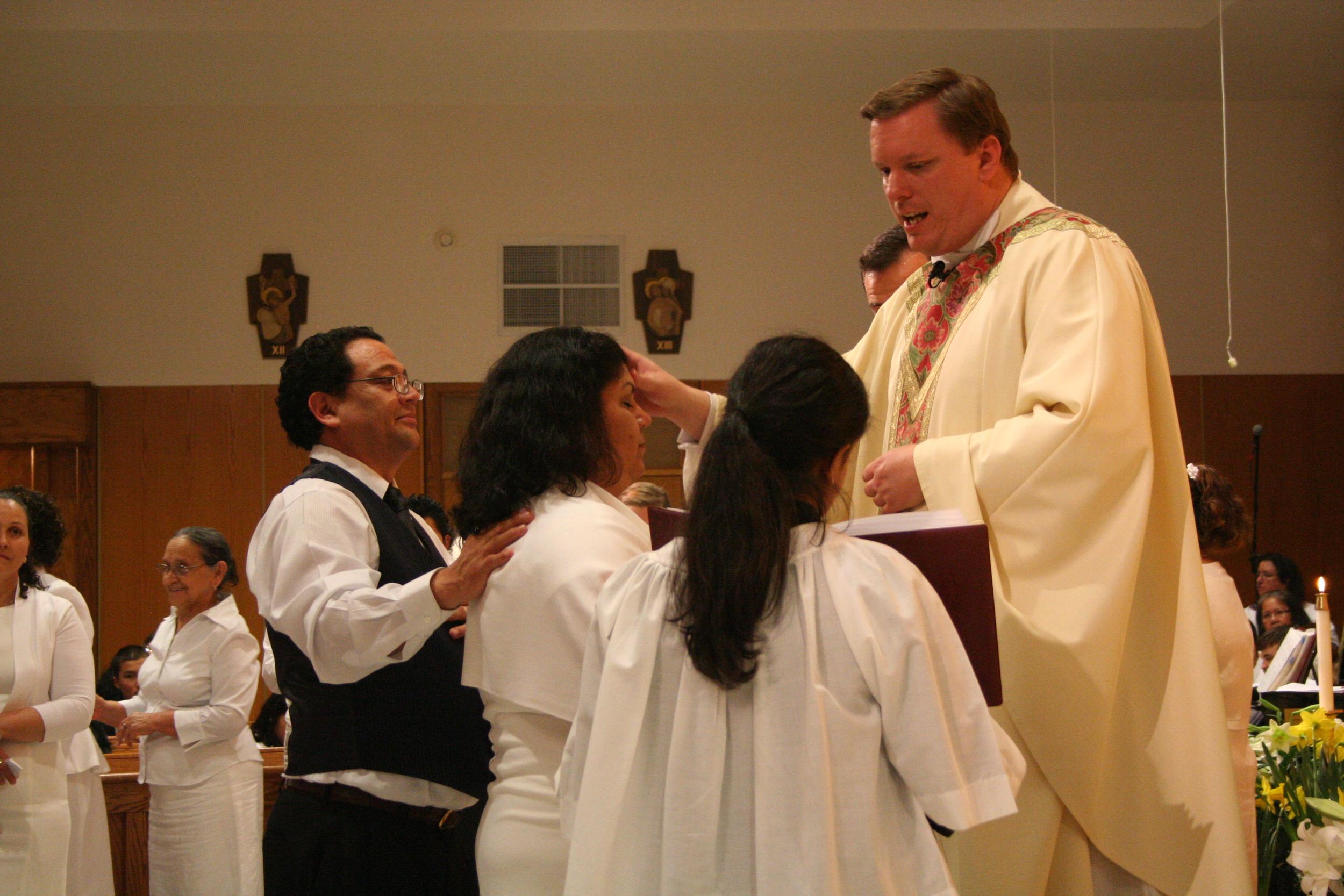 Fr. Mark S. Bialek, Pastor Emeritus, celebrates the Sacrament of Confirmation during the Easter Vigil.