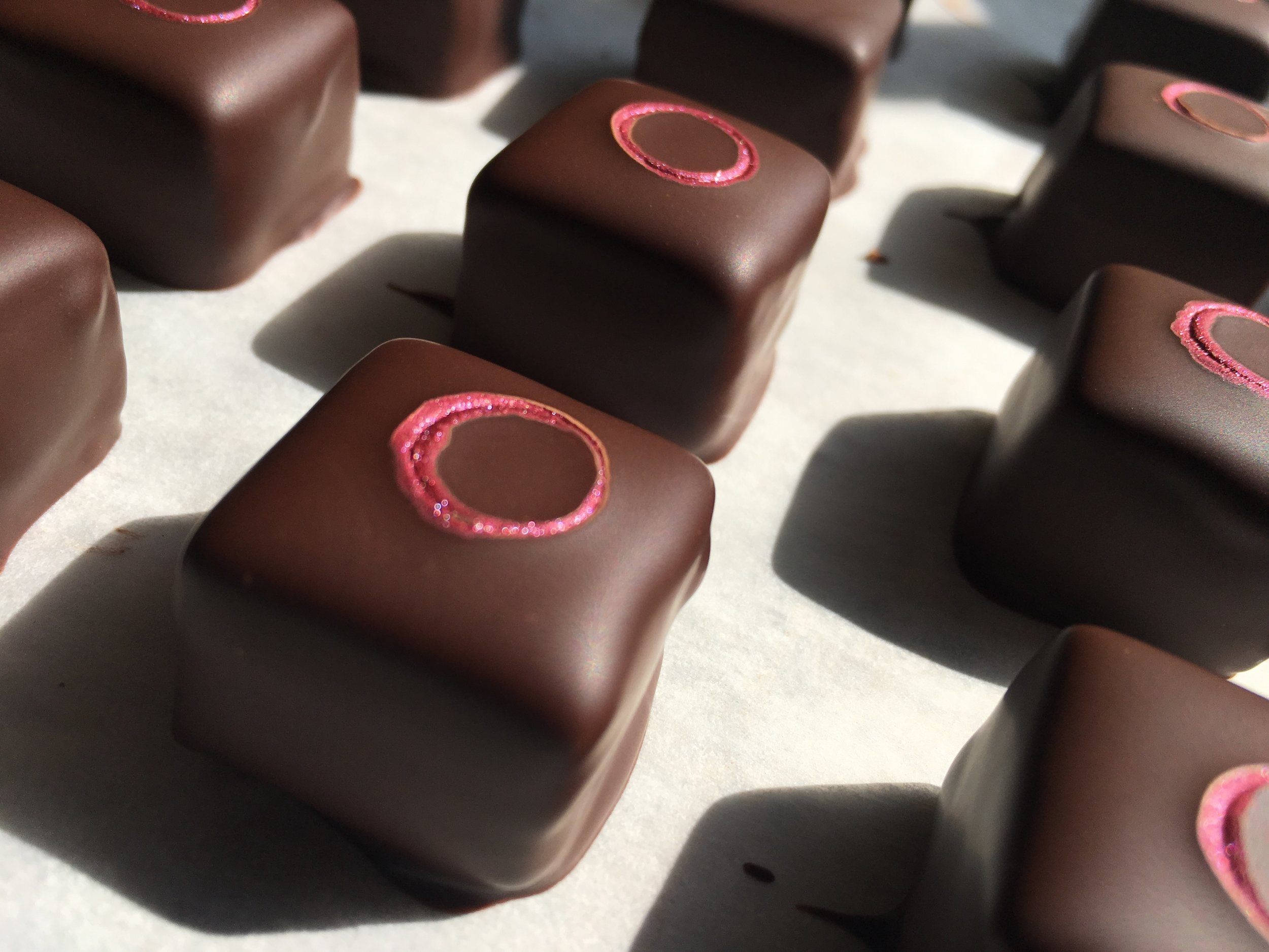 We combine a layer of sour cherry pâte de fruit, a layer of dark chocolate ganache and a layer of white chocolate ganache flavored with Kirsch to recreate the classic Black Forest taste.