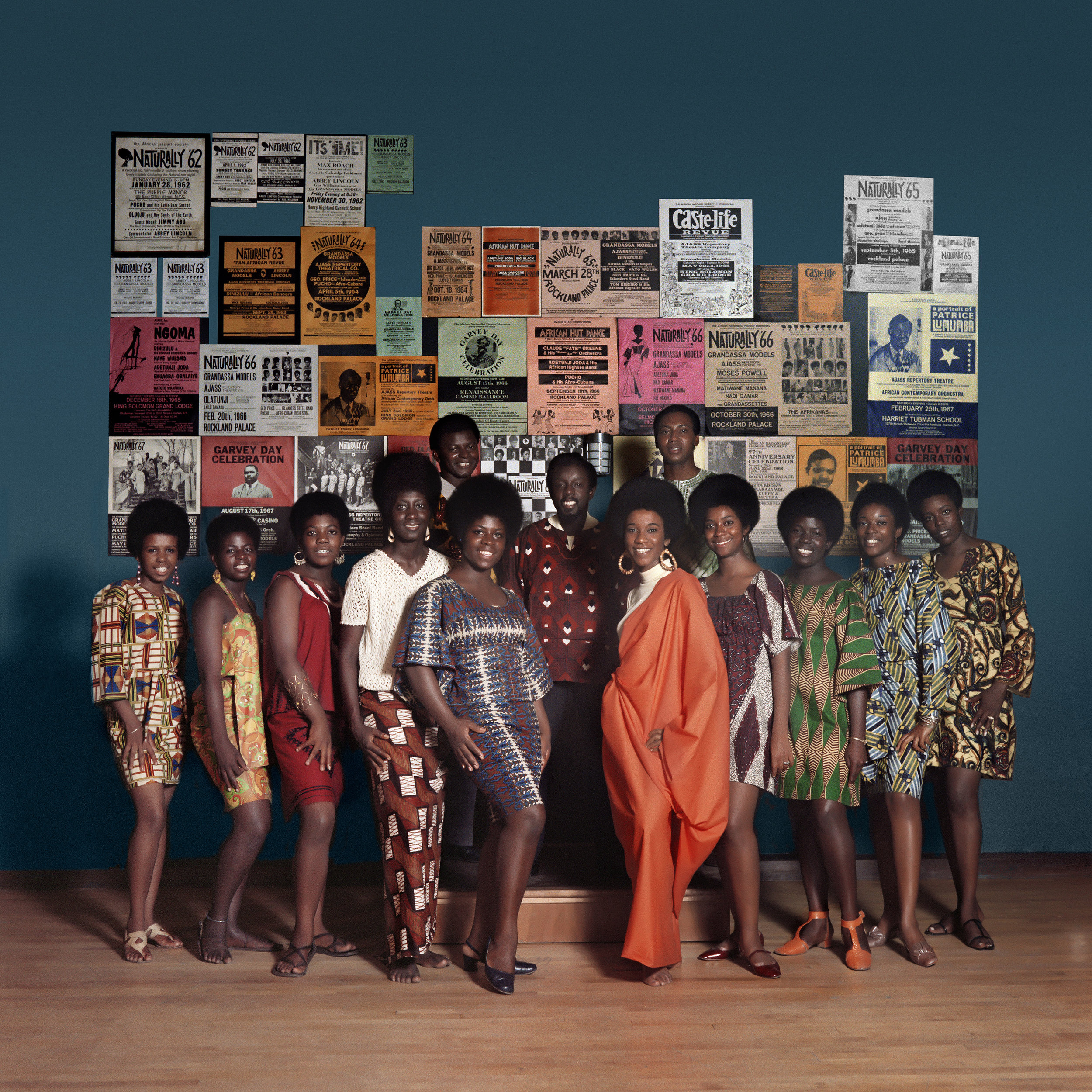 "Kwame Brathwaite. ""Naturally '68"" photo shoot, featuring Grandassa Models and founding members of AJASS. Back row includes: Eleanor Ballard, far left; Sikolo Brathwaite, third from left; Juanita McLean, fourth from left; Zeta Gathers, fifth from left; and Pat (last name unknown), third from right. Front row, left to right: Klytus Smith, Frank Adu, Bob Gumbs, Elombe Brath, and Ernest Baxter. Apollo Theater, Harlem, ca. 1968. Courtesy of the artist and Philip Martin Gallery, Los Angeles."