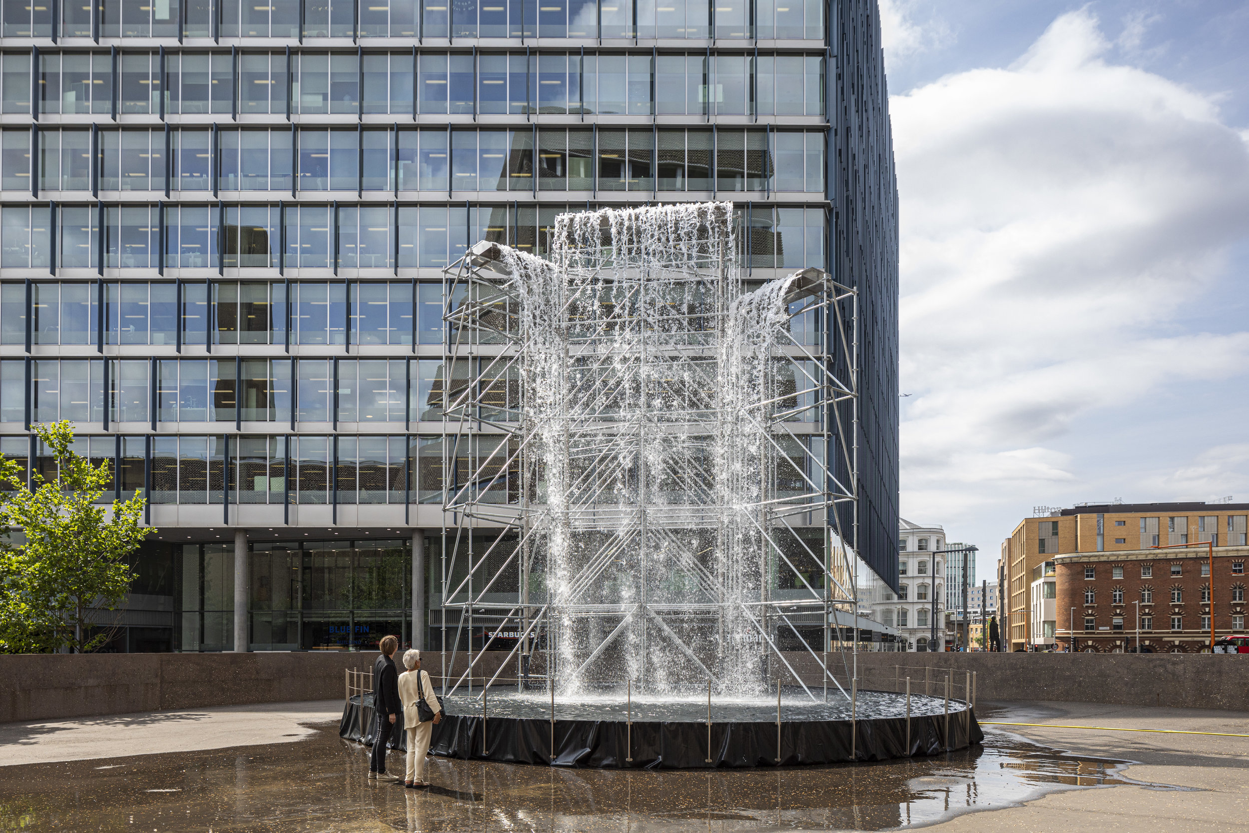 Olafur Eliasson (b.1967)   Waterfall   2019  Scaffolding, water, wood, plastic sheet, aluminium, pump, hose Height 11 metres, diameter 12 metres Courtesy the artist; neugerriemschneider, Berlin; Tanya Bonakdar Gallery, New York / Los Angeles Installation view: Tate Modern, London.  Photo: Anders Sune Berg  © 2019 Olafur Eliasson