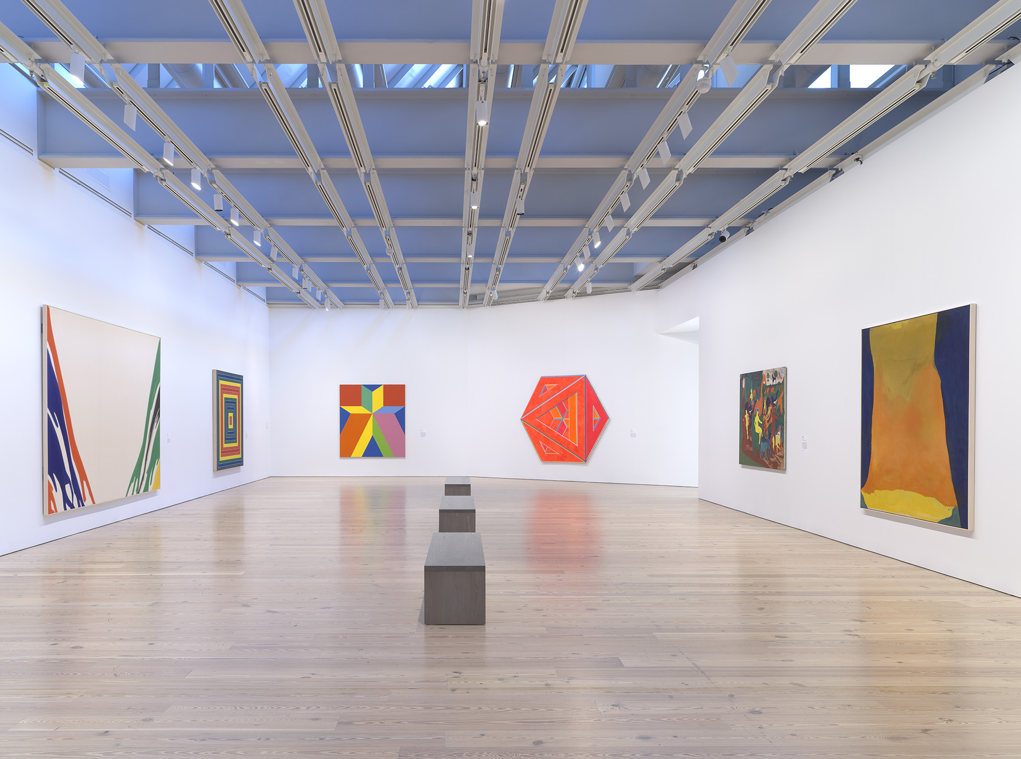 Installation view of  Spilling Over: Painting Color in the 1960s  (Whitney Museum of American Art, New York, March 29-August 2019). From left to right: Morris Louis,  Gamma Delta , 1959-60; Frank Stella,  Gran Cairo , 1962; Miriam Schapiro,  Jigsaw , 1969; Alvin Loving,  Septehedron 34 , 1970; Bob Thompson,  Triumph of Bacchus , 1964; Helen Frankenthaler,  Orange Mood , 1966. Photograph by Ron Amstutz