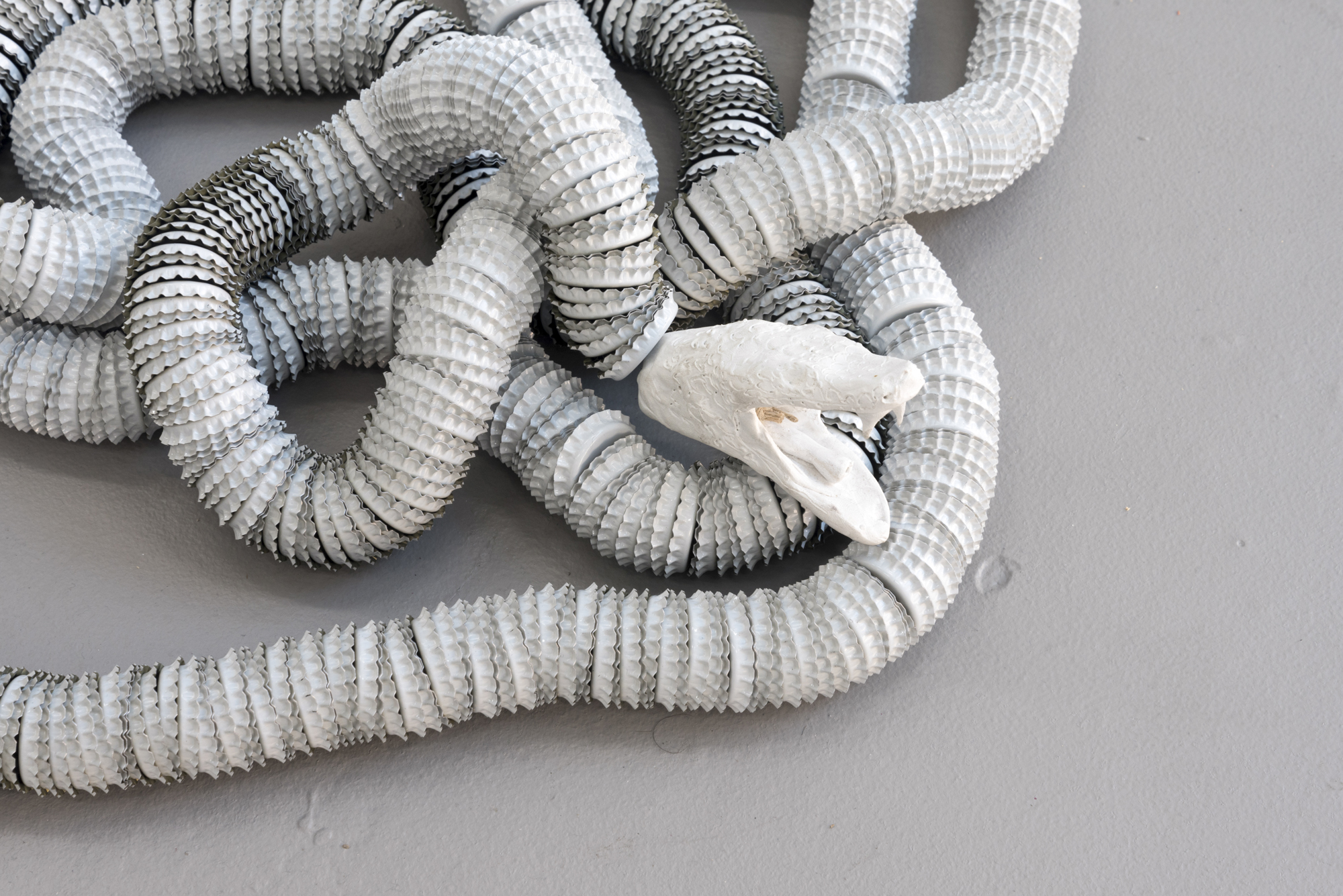 Preparing for the Unknown  (Dream Snake)  2019 polymer clay, hemp string, bottle caps 20 feet long, installation dimensions variable