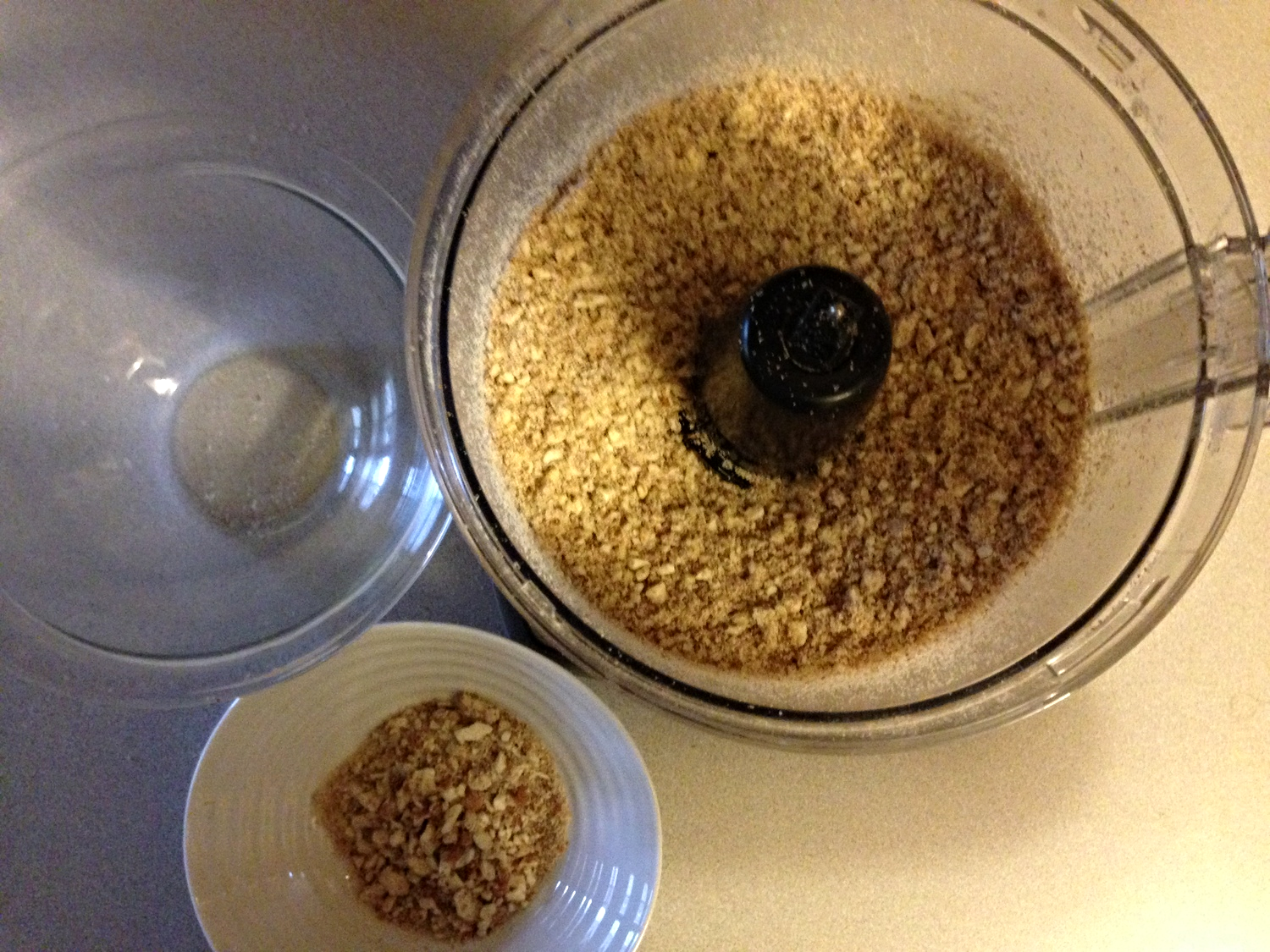 Ground almonds in food processor for homemade, healthy nut butter.