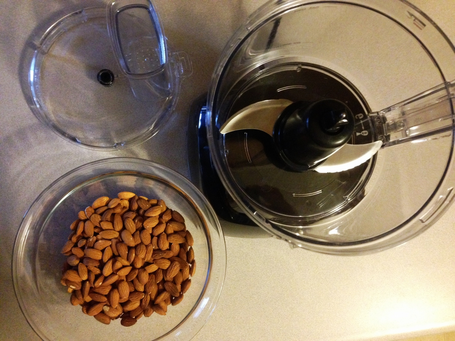 Food processer and almonds for making homemade healthy nut butter - health food how-to!