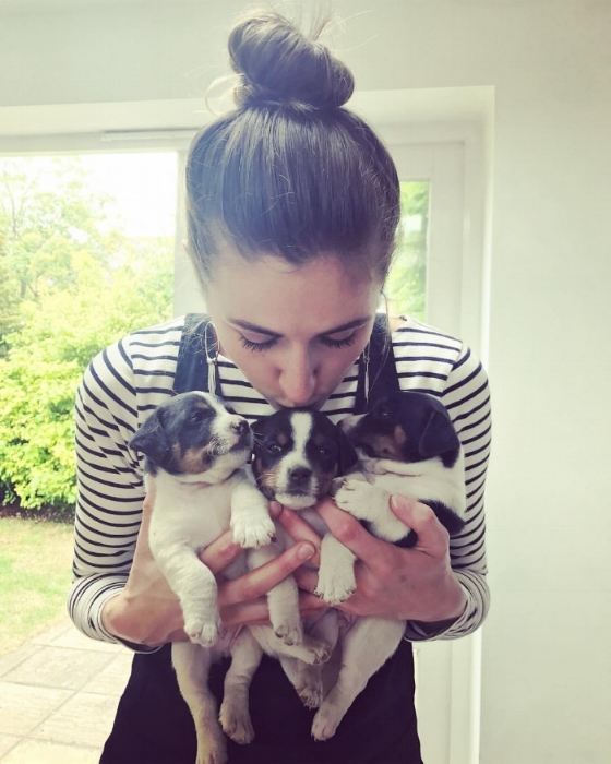 Photo of health and wellness coach Georgie Muir with 3 puppies in her arms