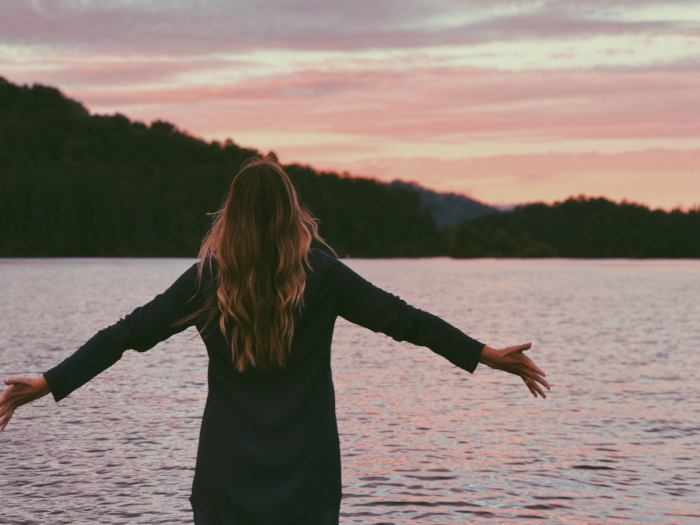 photo of girl looking out over lake, arms spread wide.