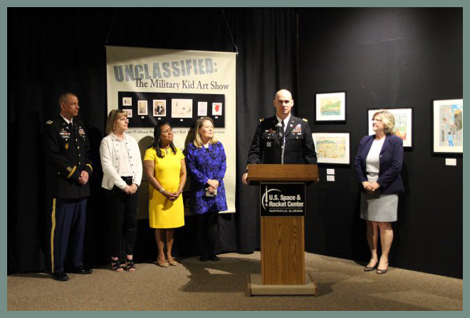 """Garrison commander Col. Bill Marks talks about the exhibit """"Unclassified: Military Kid Art Show"""" Thursday during its opening at the U.S. Space & Rocket Center. With him, from left, are Col. William Darby, commander of Fox Army Health Center; Marks' wife, Laurie; Linda Via, wife of Gen. Dennis Via, commander of the Army Materiel Command; exhibit co-curator Donna Musil and Dr. Deborah Barnhart, director of the U.S. Space & Rocket Center."""