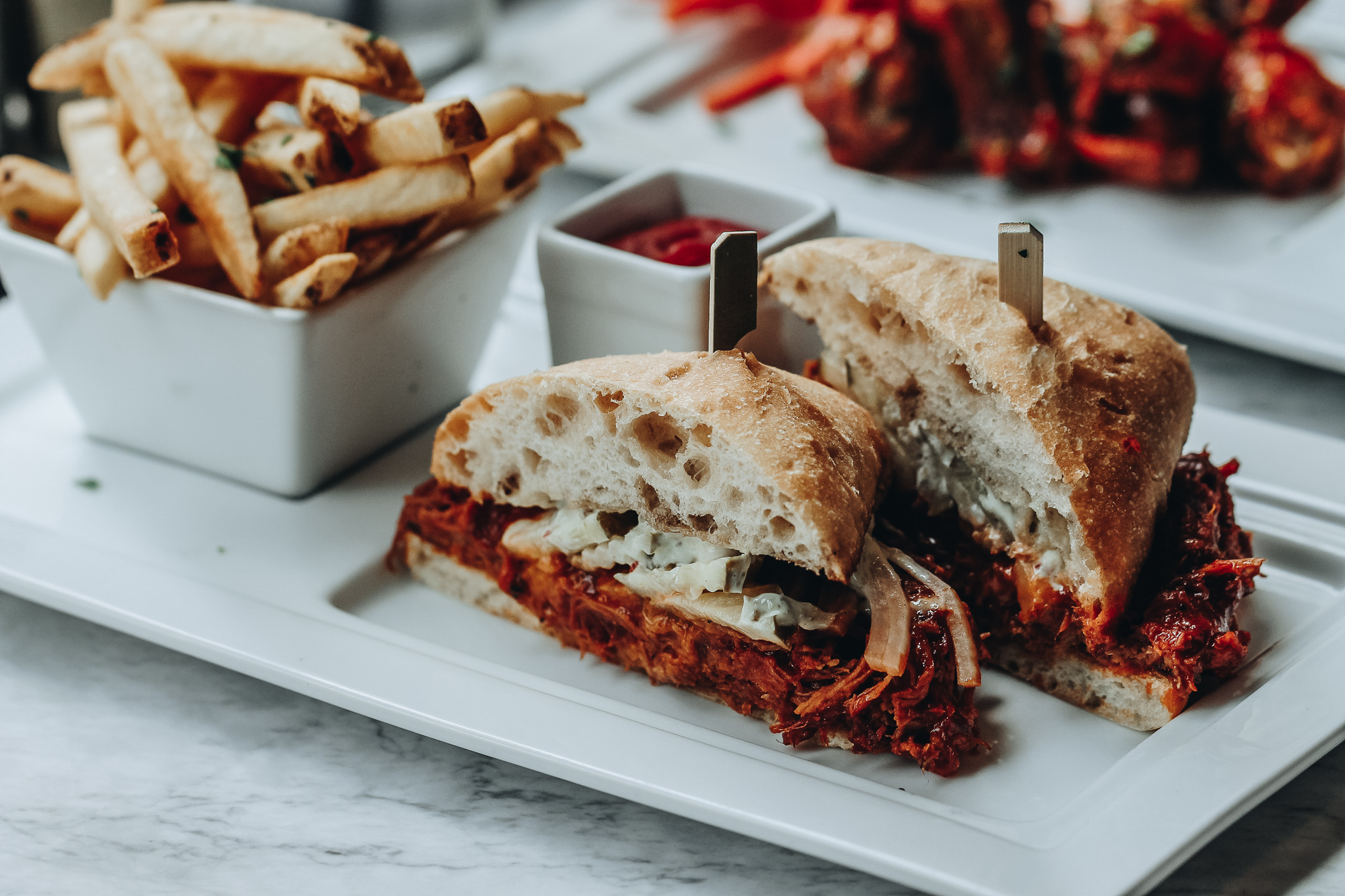 Cambria Dallas Hotel    Smoked Pulled Pork Sandwich  with Spicy Pickles, Onion, Jalapeno Aioli and Fries