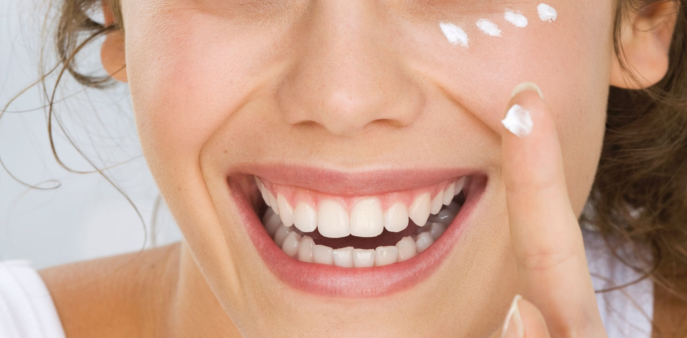 6967765Young-woman-putting-cream-on-face-smiling-2.jpg