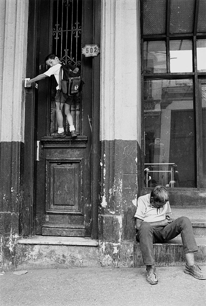 Boy Ringing Doorbell,  Havana, Cuba, 2000  Archival pigment print.  20 x 13 3/8 inches