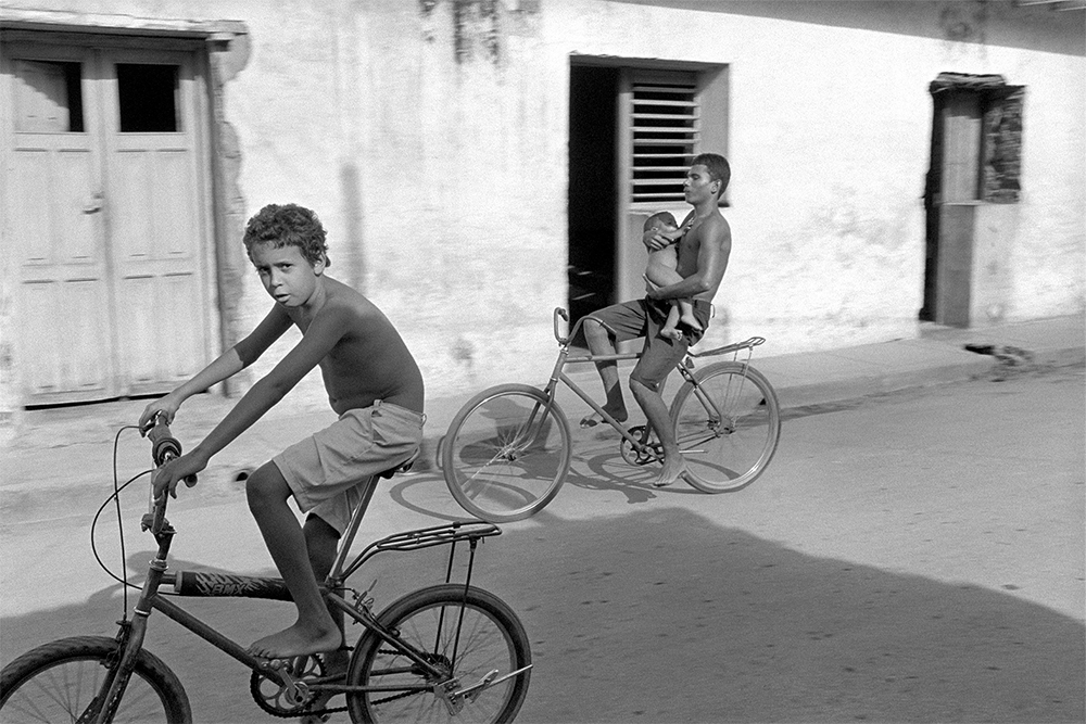 Boy on Bike with Baby , Trinidad, Cuba, 2000  Archival pigment print.  13 3/8 x 20 inches