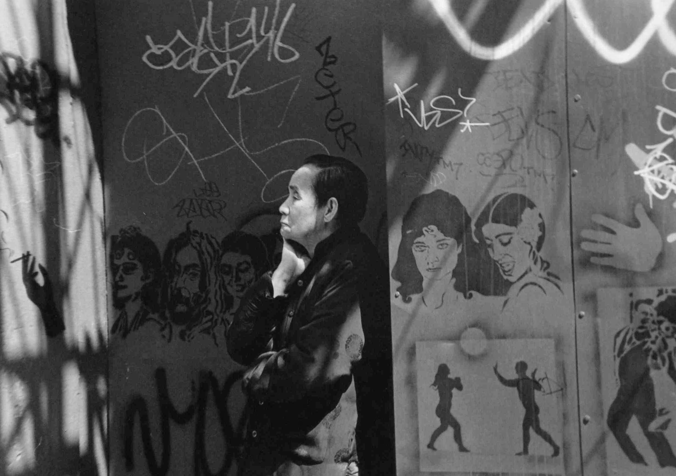 Woman on Mott Street with Graffiti, New York , 1995  Gelatin silver photograph.   11 7/8 x 17 3/4 inches