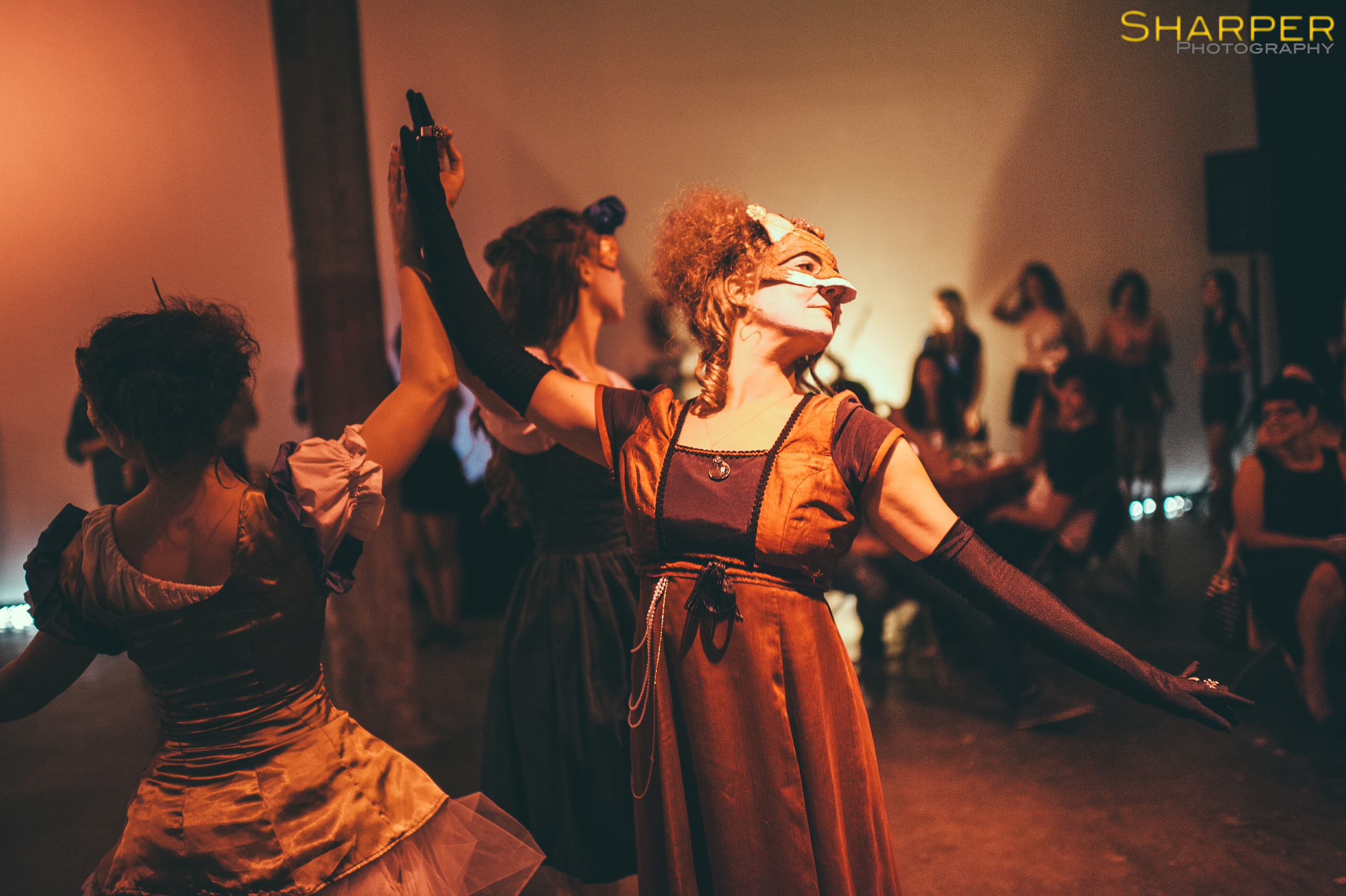 Dancers perform in Shakespearean masks during interactive theater performance in downtown Austin