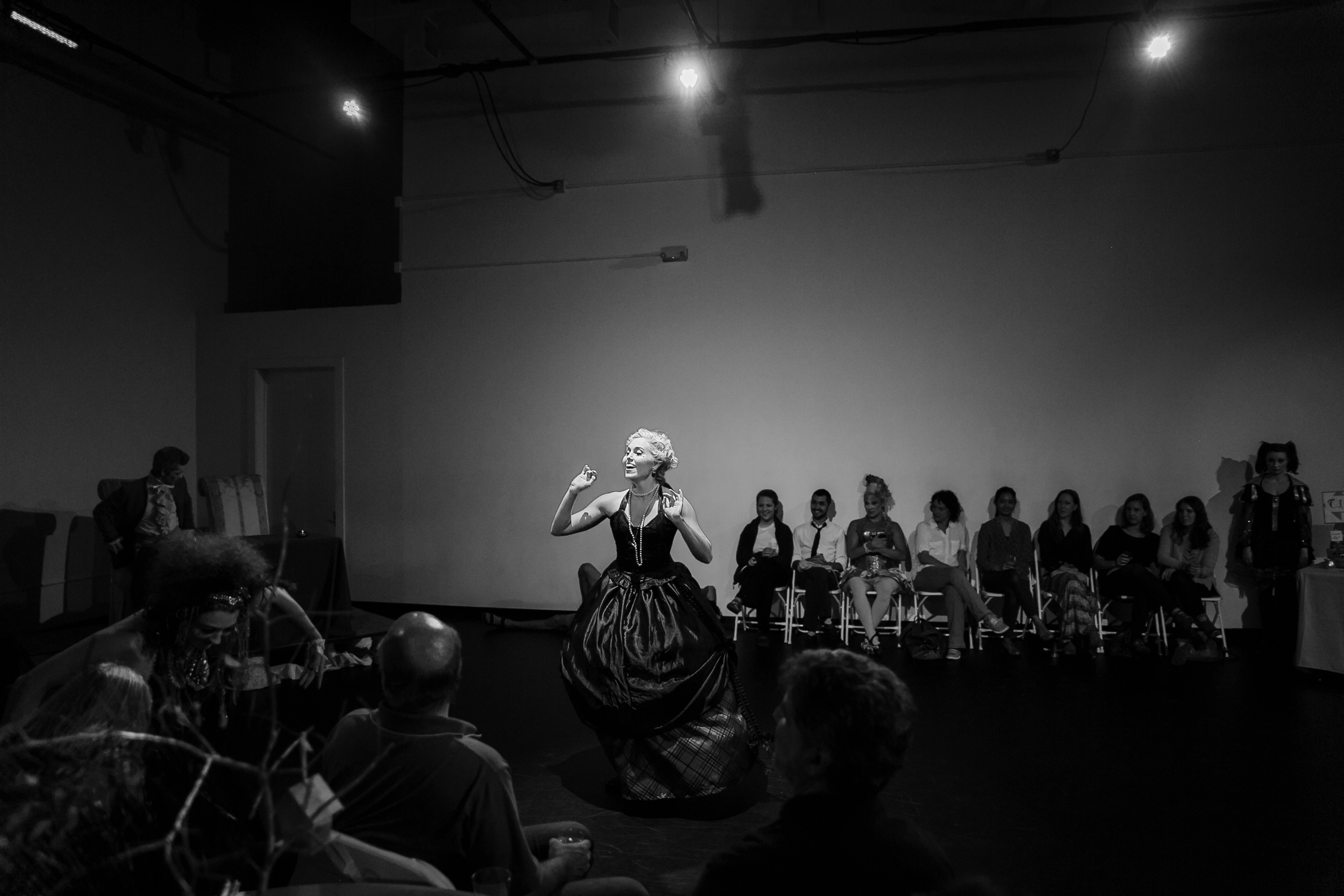 Black and white photo of actor speaking to audience at NunaMaana immersive dance theater performance