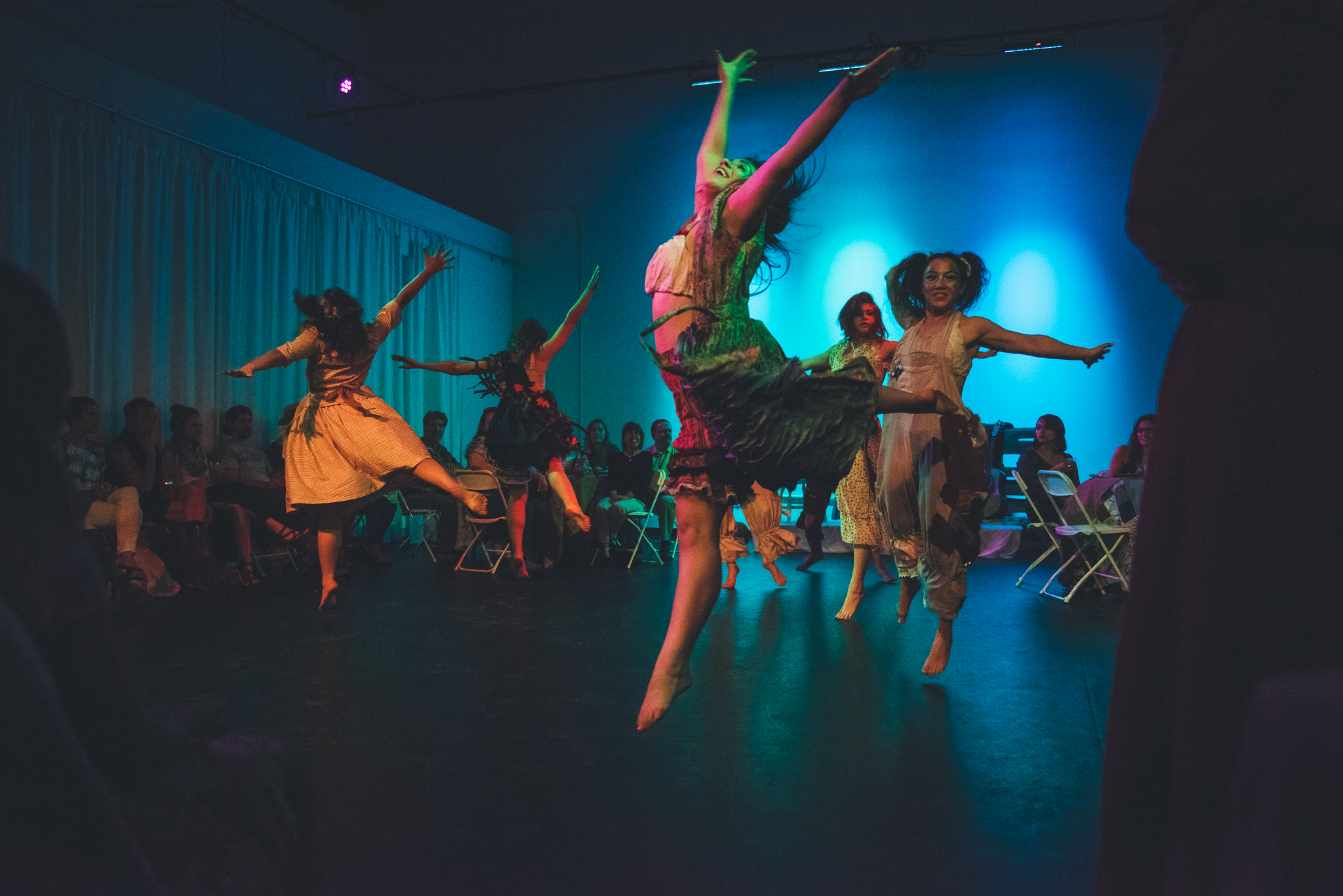 Dancers leaping during Austin Wild West theater performance