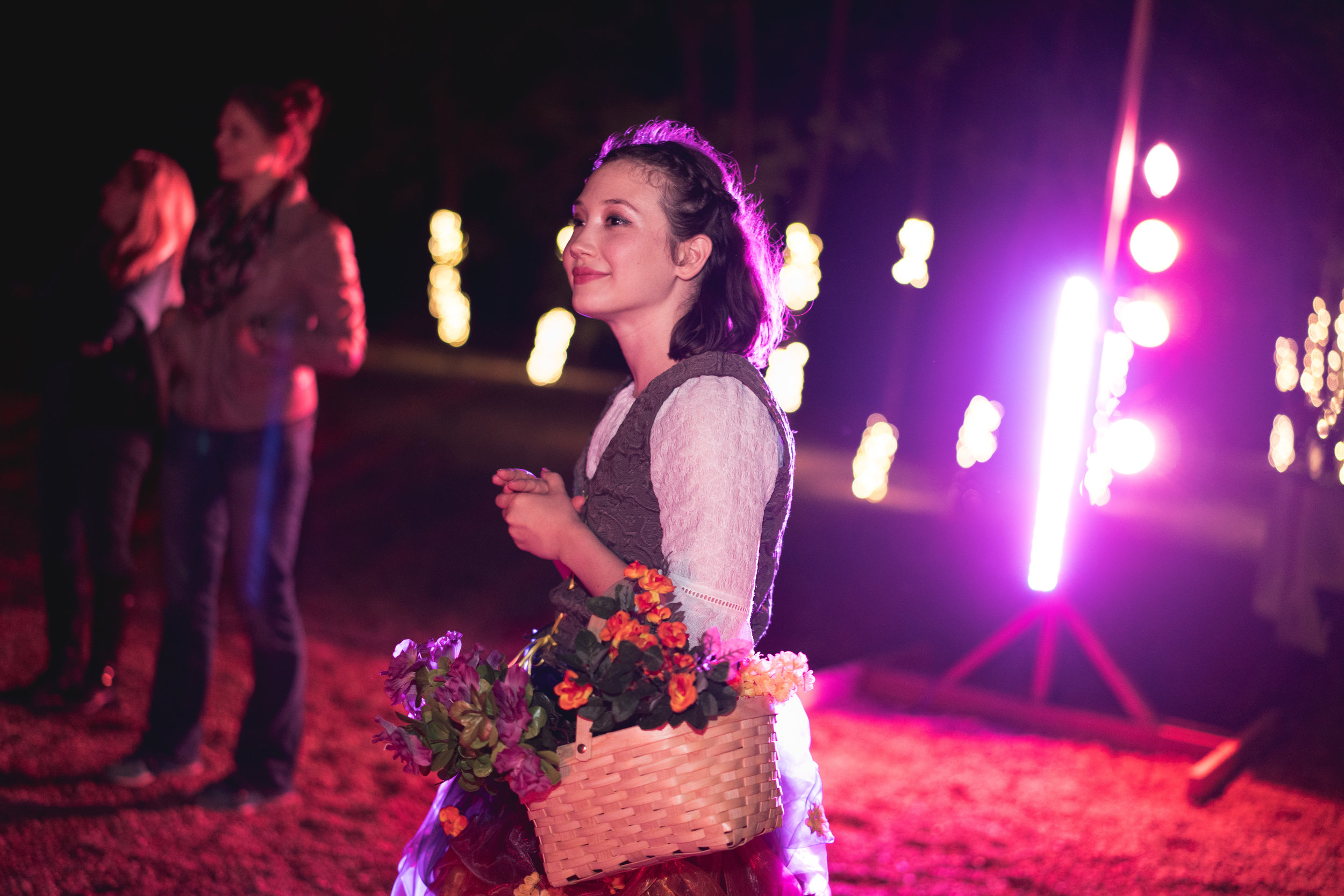 Renaissance actor carries flower basket during Austin dance theater performance outside