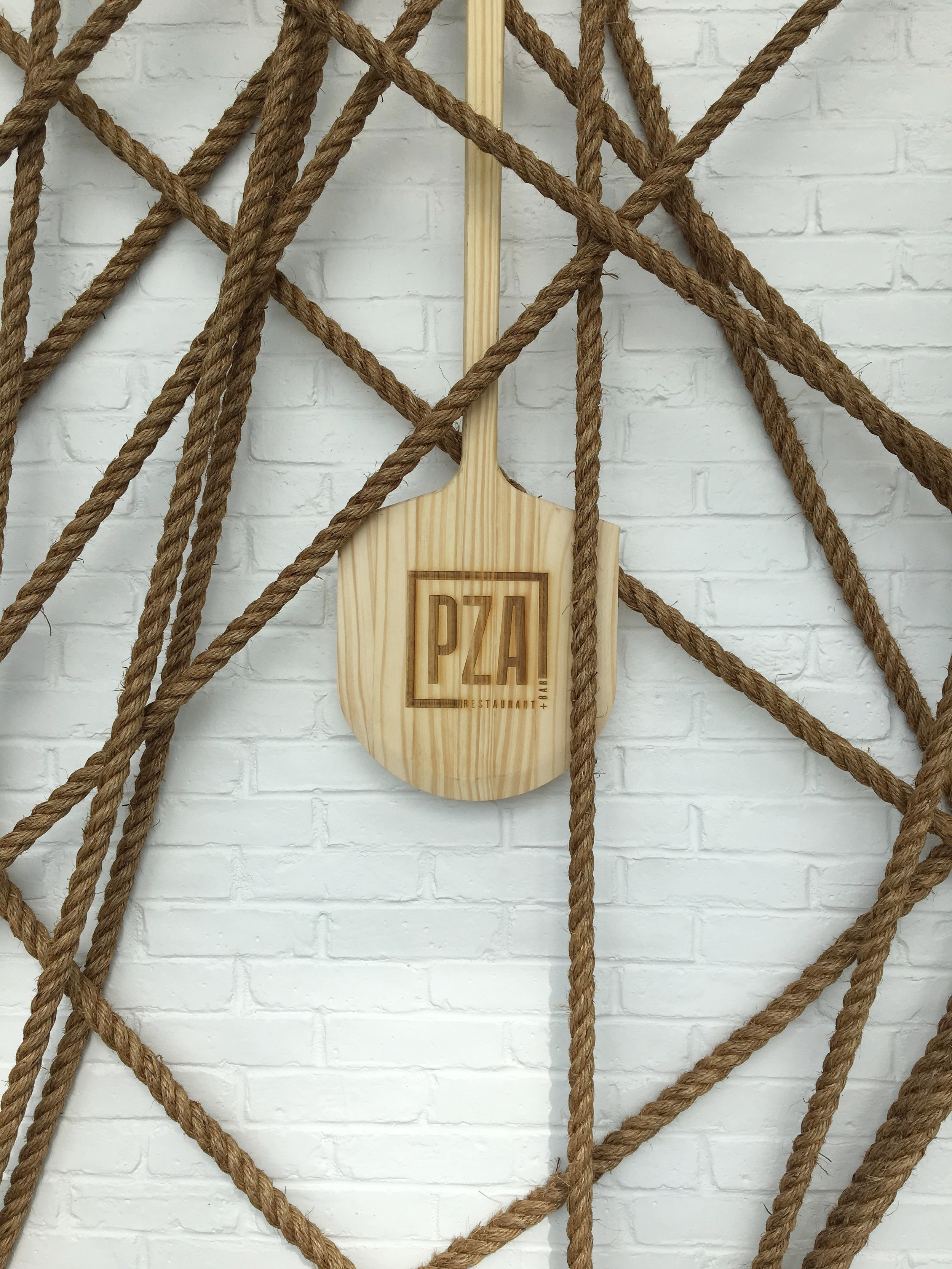 PZARestaurant,Toronto - In collaboration with Rob Southcott Studio and II BY IV Design, our studio designed and produced an exciting installation featuring over 100 hand charred Pizza Peels and over 1200 ft of Rope that hover over the main dining area of this unique space.