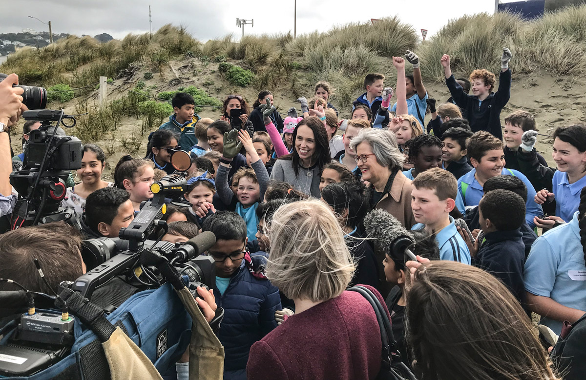 PM Jacinda Ardern and Associate Environment Minister Eugenie Sage celebrate the announcement by joining the kids for a beach clean-up.