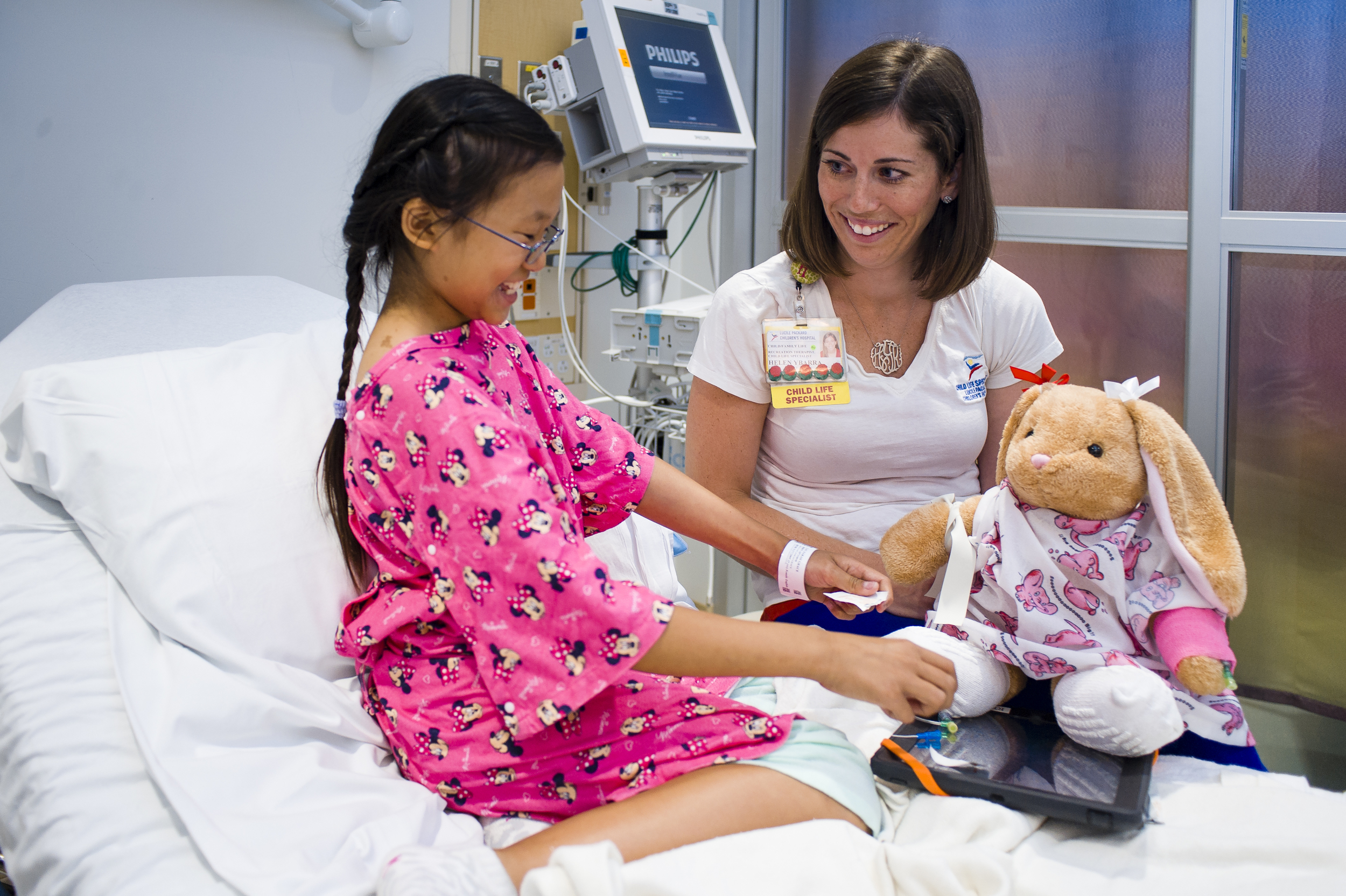A child life specialist demonstrates an upcoming procedure on a stuffed animal.