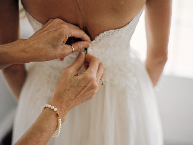 Bride-getting-into-her-dress-mother-helping.jpg