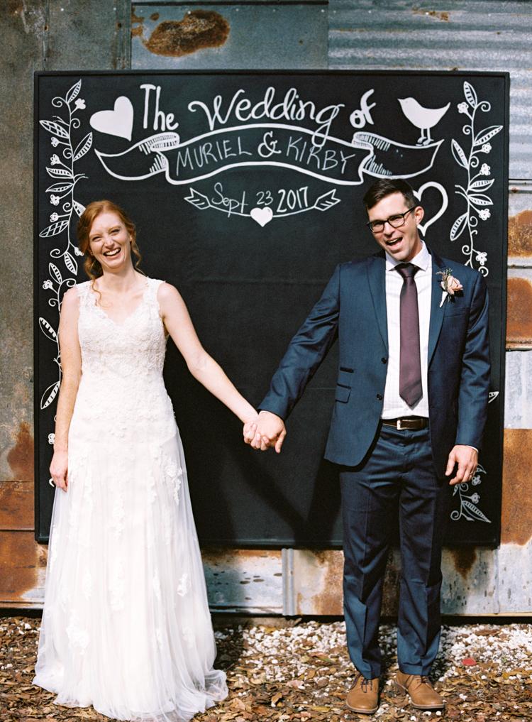 couple-with-wedding-chalkboard-bridle-oaks.jpg