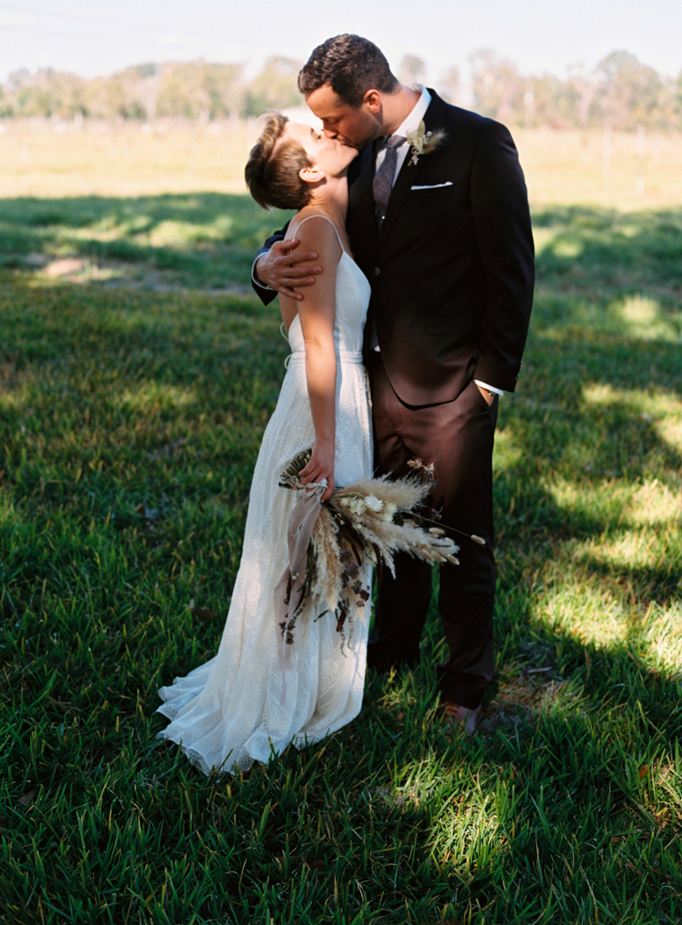 natural-bride-and-groom-kiss-in-a-field.jpg