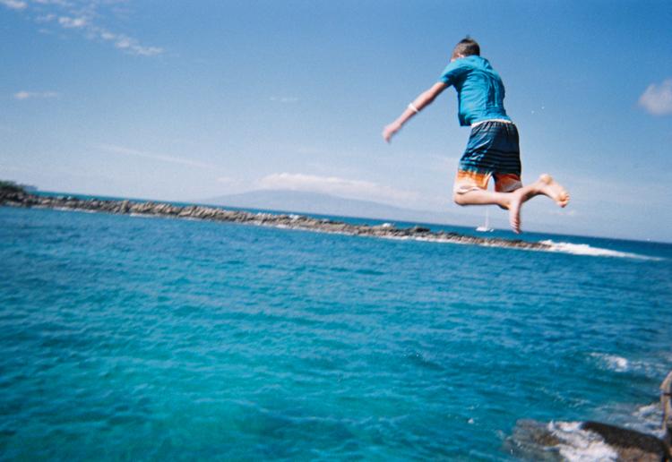 boy-in-blue-shirt-jumping-into-maui-ocean.jpg