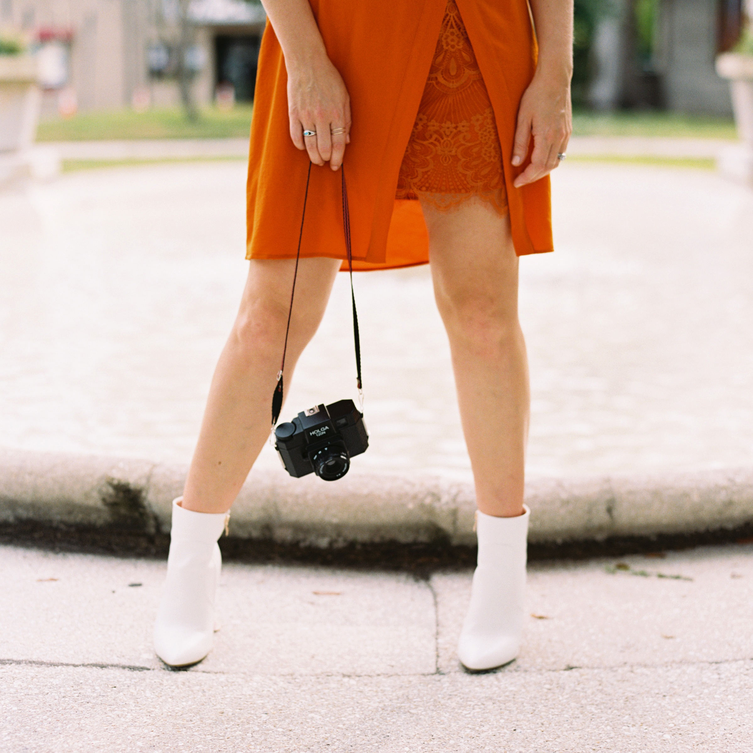 woman in orange dress and white boots holding a camera