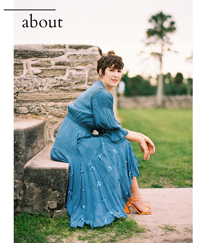 E M Anderson in a blue dress sitting on stairs in st augustine