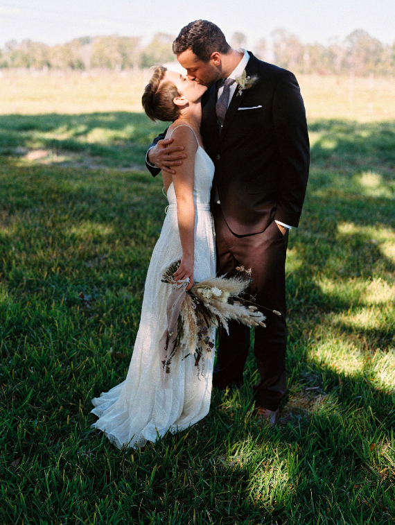 Boho bride kissing her groom in a field at Congaree and Penn wedding