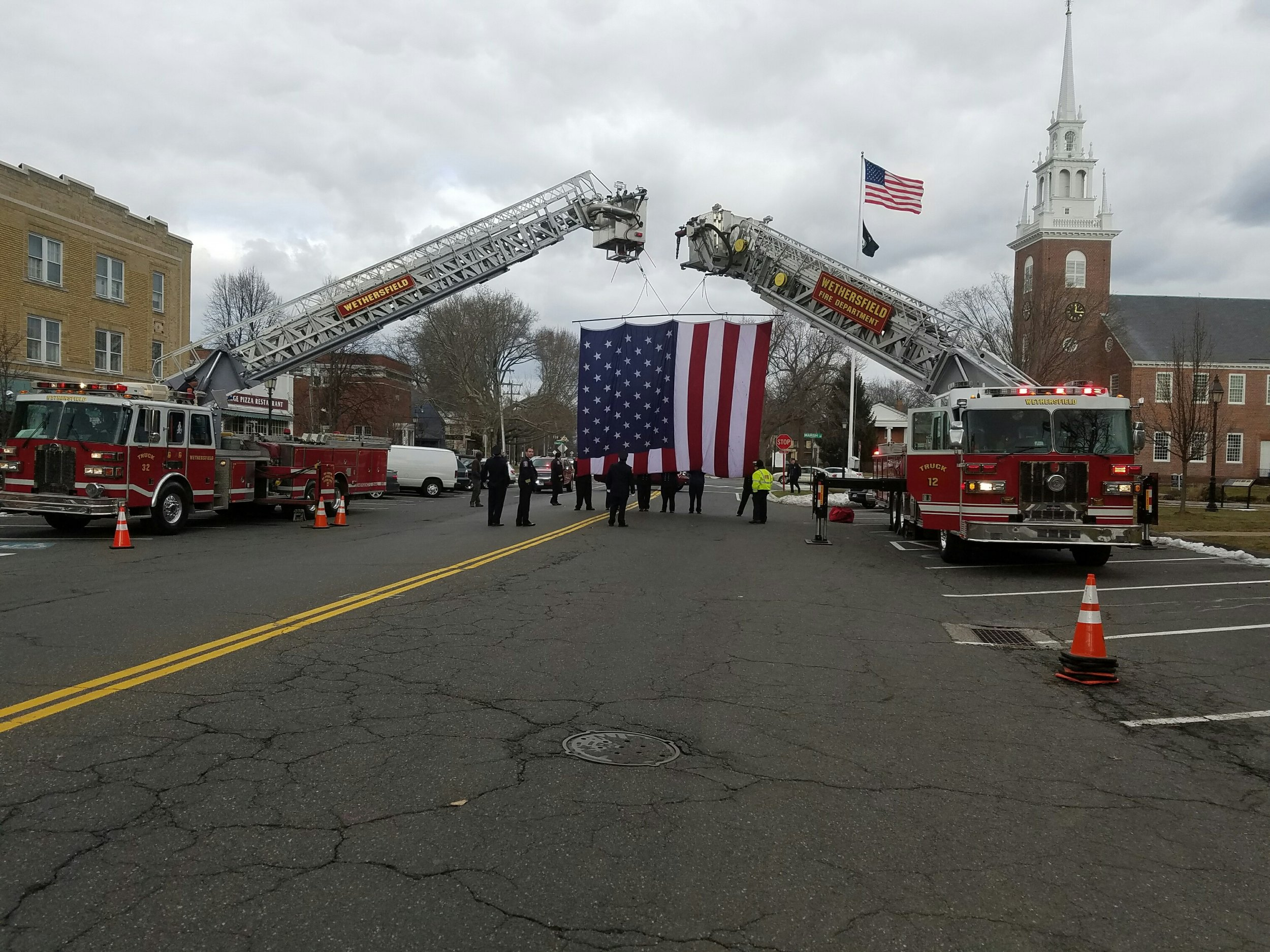 Firefighters begin raising the American Flag for the funeral procession of former Chief John McAuliffe.