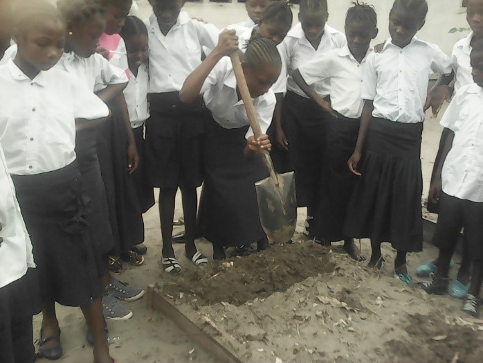 Students at the College des Savoirs start a garden bed.