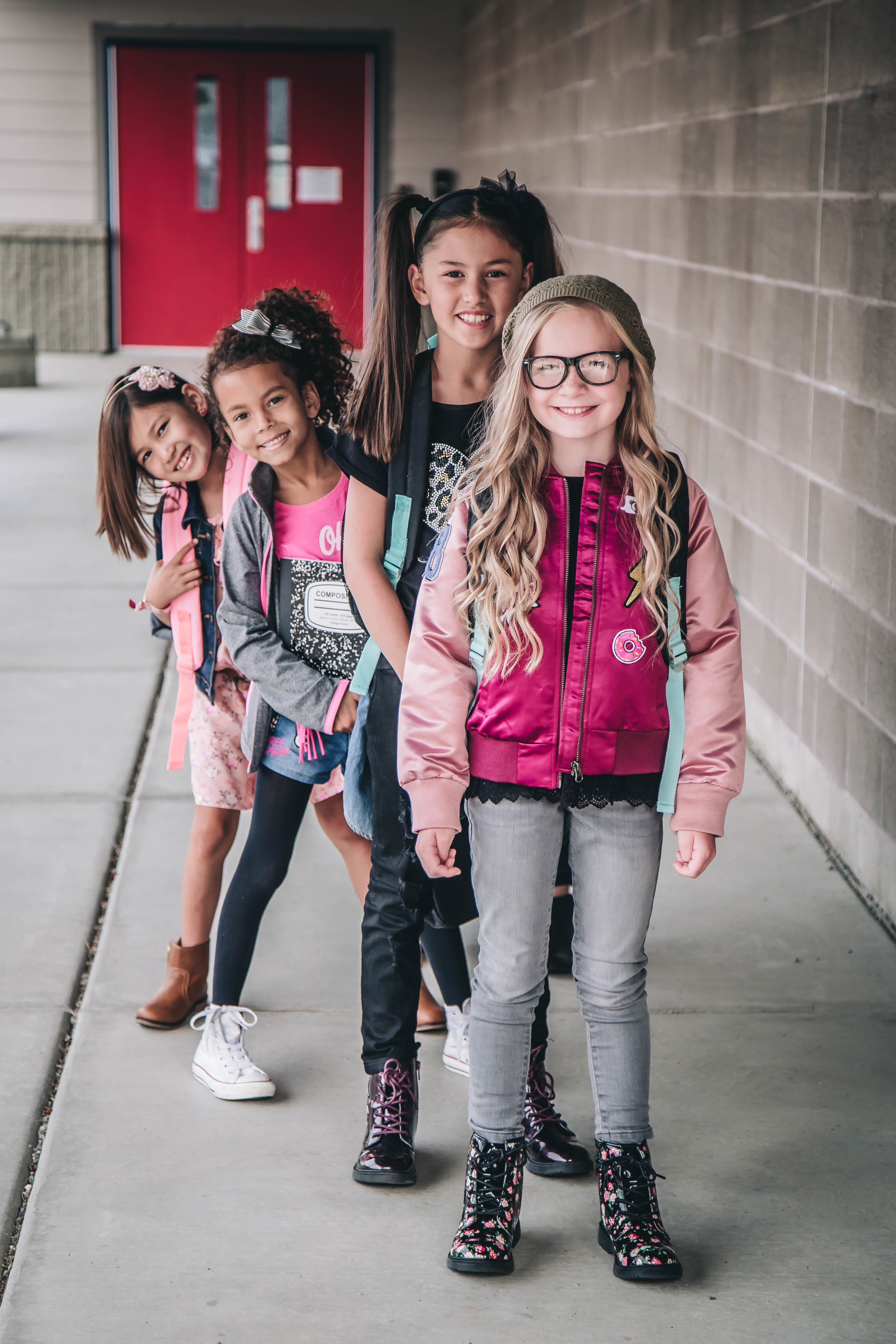 Geek Goals - Who says nerdy can't be cool?! Scout is dressed to impress (her science class buddies) in her brand new varsity bomber jacket. This mathlete is on her way to earning her letter in academics and she's proud of it! She is layered up in a trendy lace hem knit top, granite jeggings, and floral combat boots. Scout is looking confident and cool on her way earning straight A's! #girlgenius