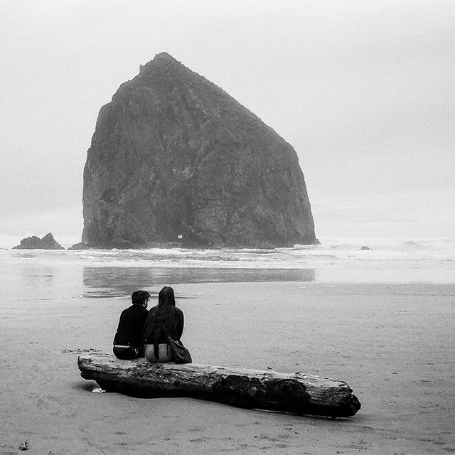 a couple gazes out at Haystack Rock on a cloudy day, on film // leica m4 w/ ilford hp5 400