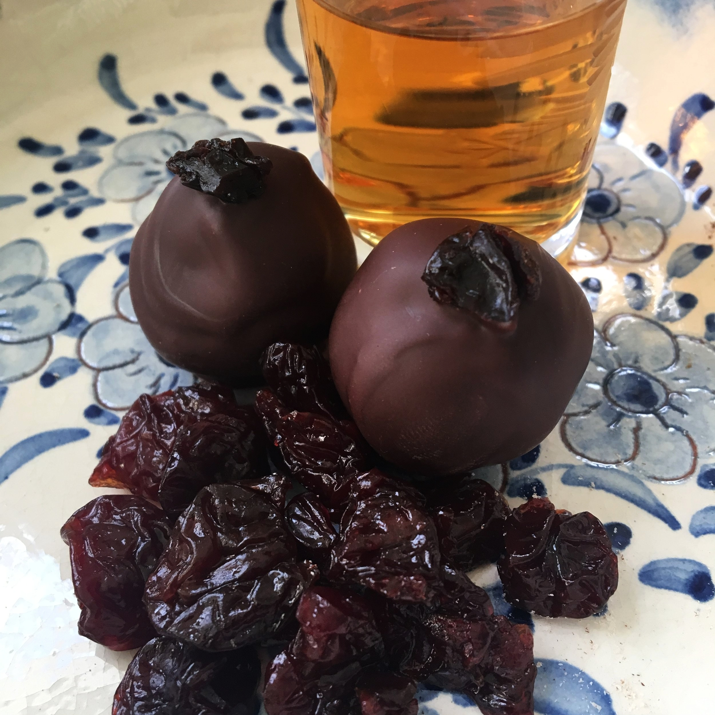 Bourbon Cherry - Tart dried cherries soaked in a secret Markers Mark bourbon blend, chopped and rolled into a rich ganache, dipped in dark chocolate, and topped with a piece of cherry. CONTAINS ALCOHOL