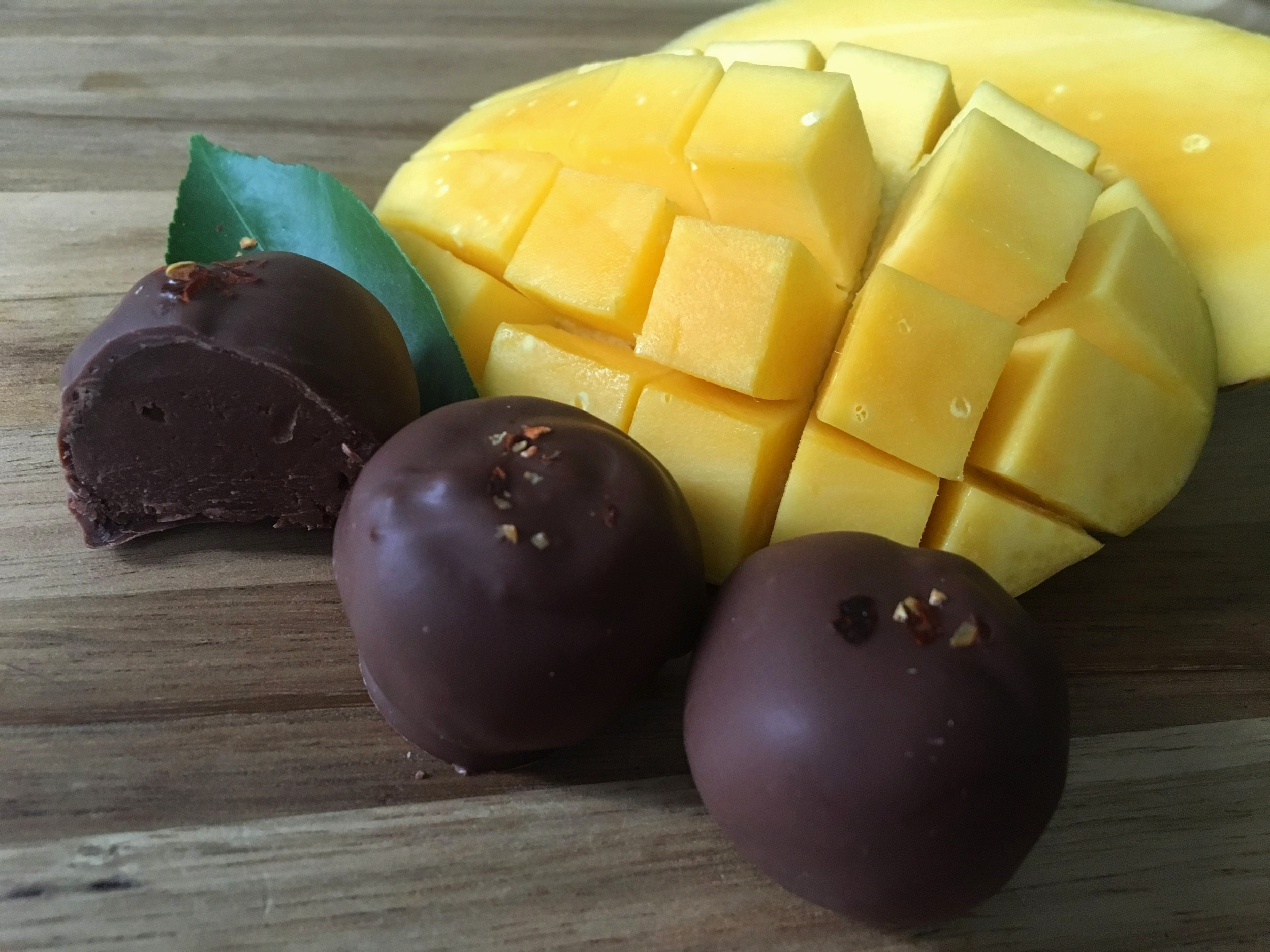 Mango - SEASONAL FLAVOR Available in Spring. Real mango blended in ganache dipped in milk chocolate and finished with a touch of chili pepper on top.
