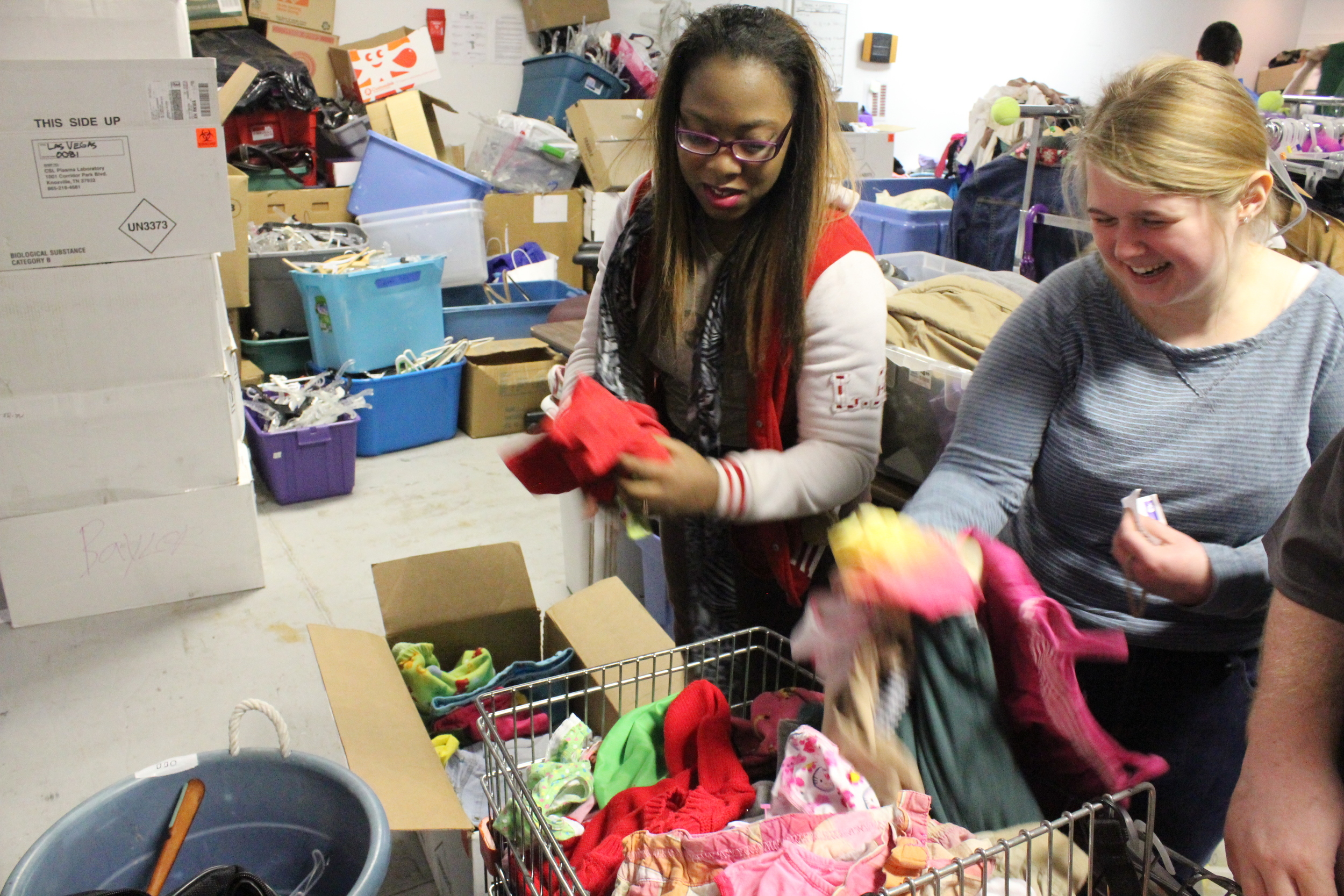 """Mirissa Lee (left) is a Work Adjustment client at Goodwill. She works side-by-side with CDC student, Emma McKinney. Mirissa helps Emma identify the tag colors. """"We like to talk when we work,"""" Mirissa said. """"We laugh a lot."""" With a giggle, Emma added, """"Especially around underwear!"""""""