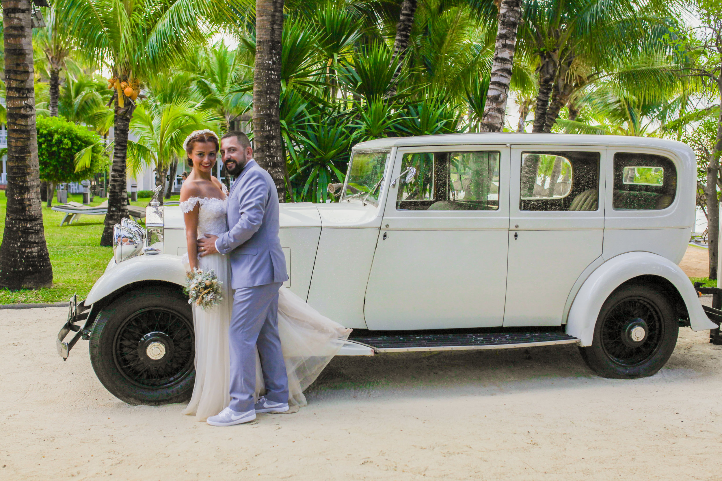 Married couple posing with vintage car at LUX belle mare