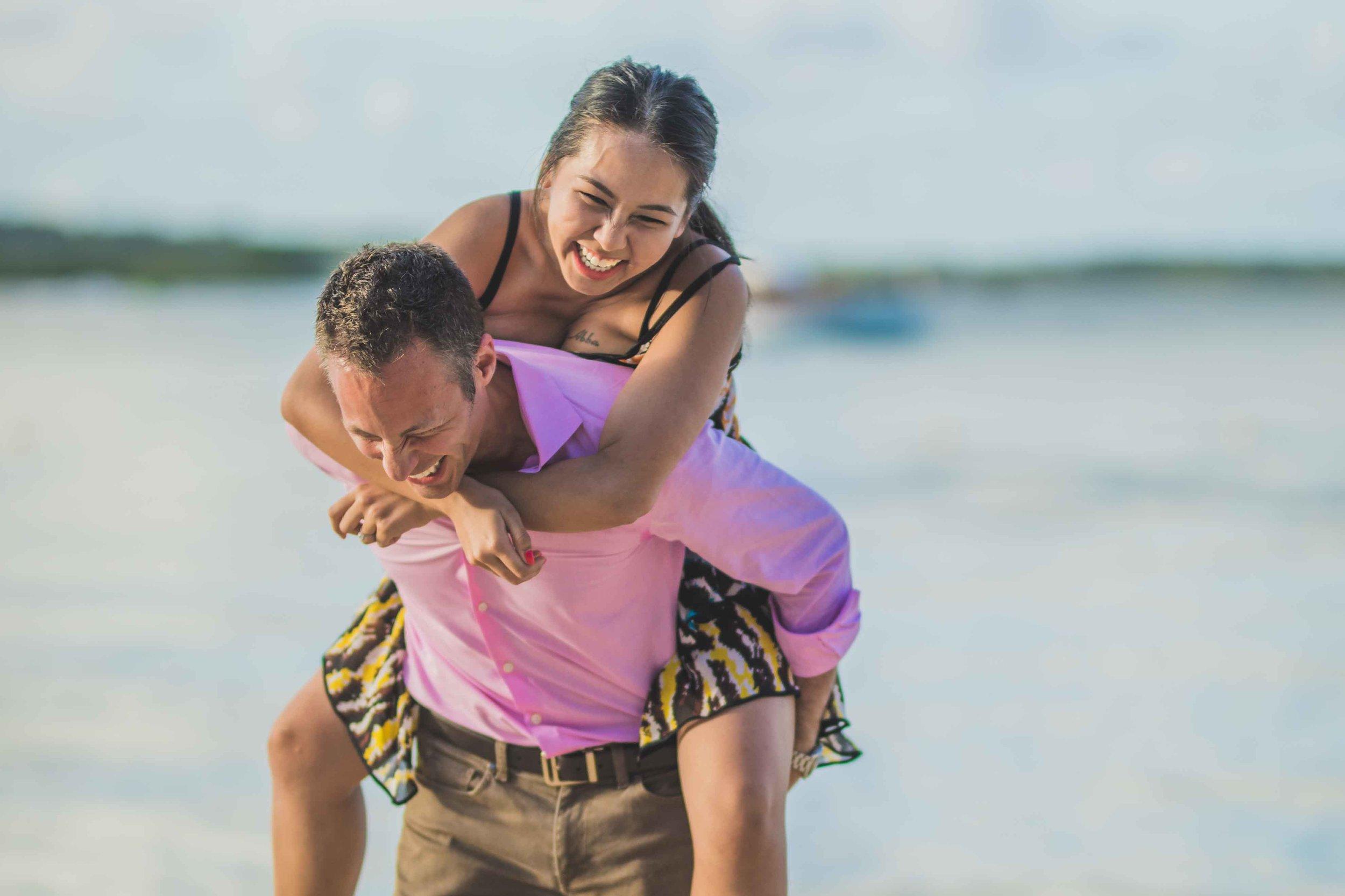 Wife on husband's back laughing on honeymoon