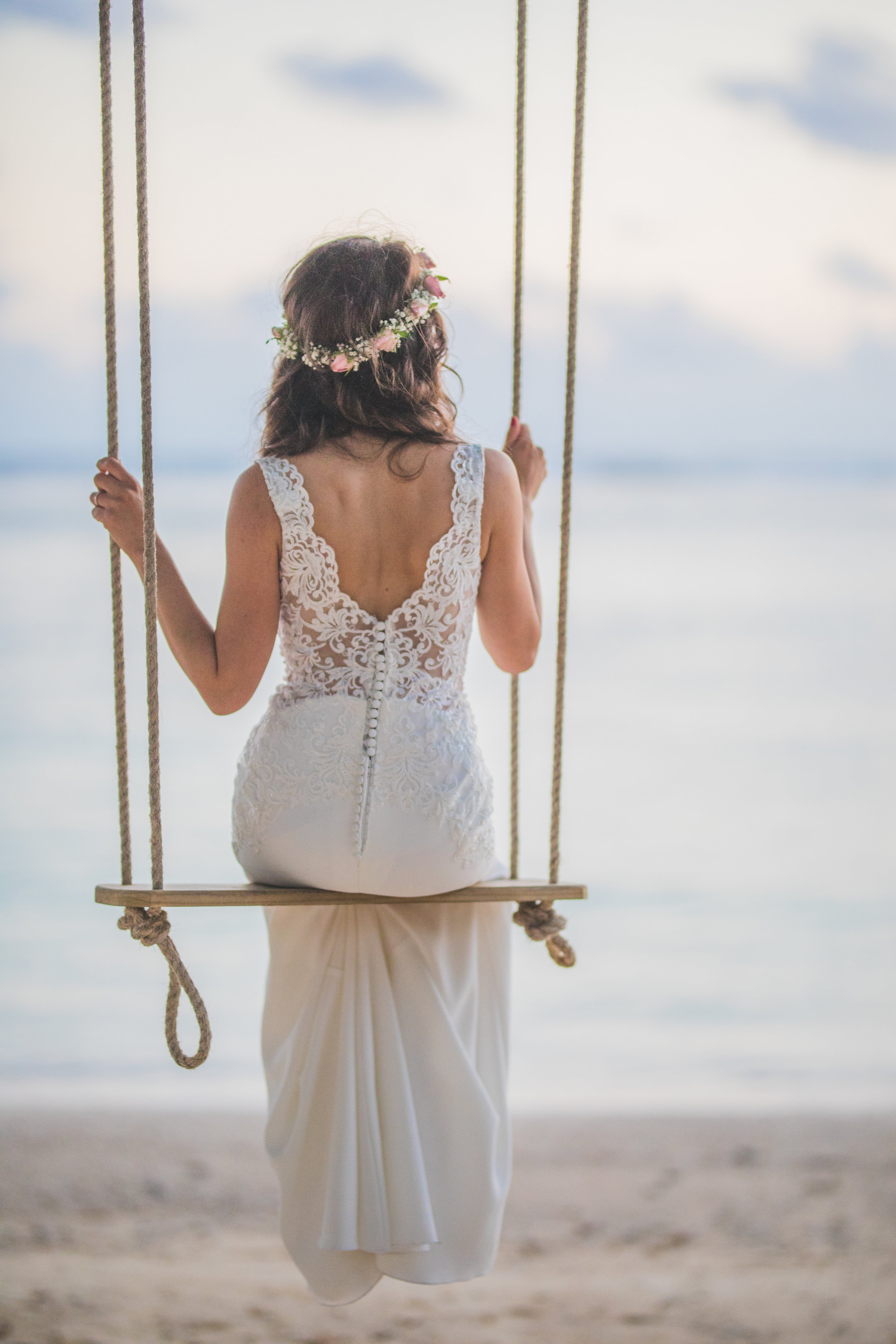 Bride's back on swing looking a Mauritian sea