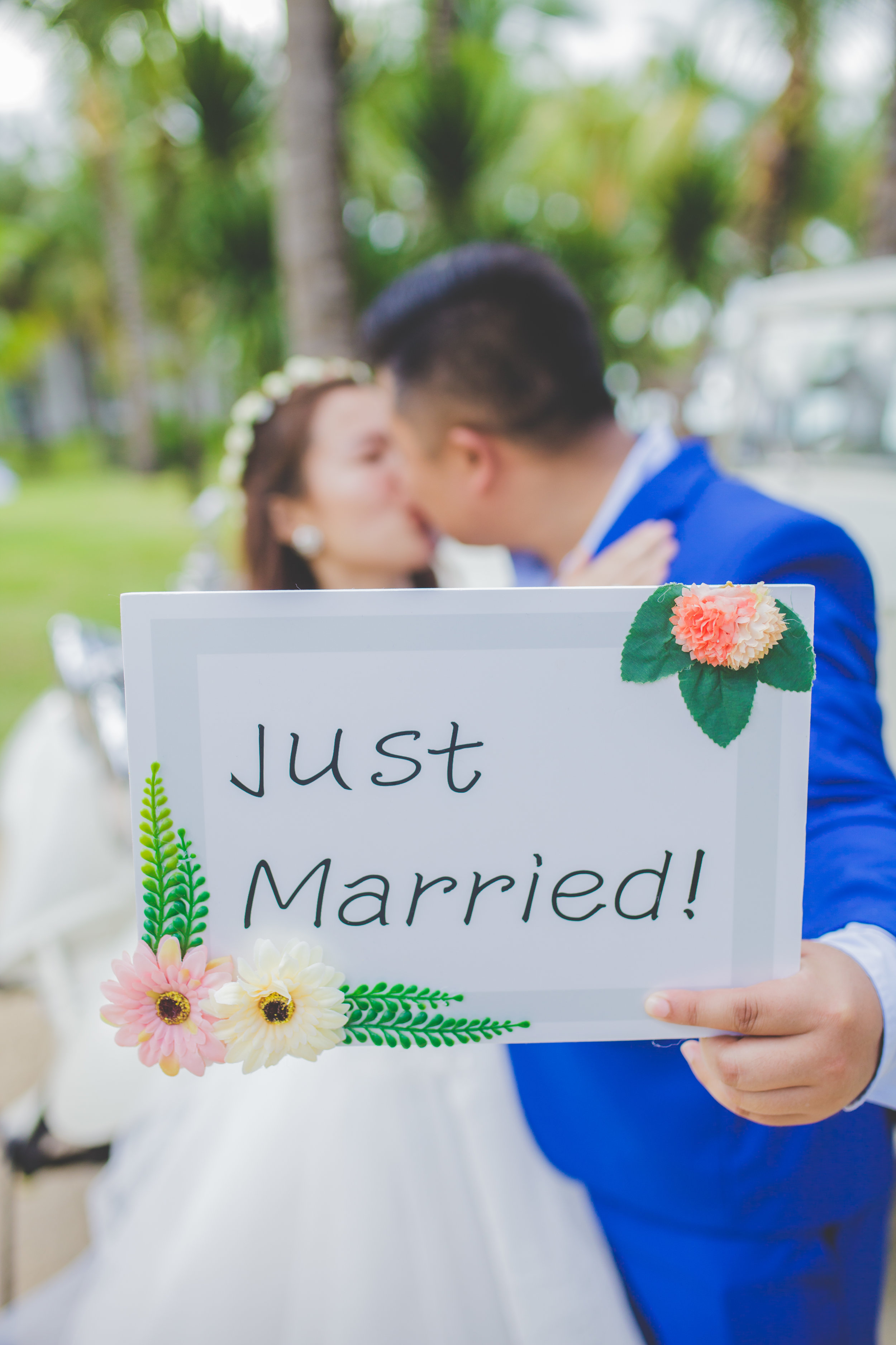Couple Kissing and holding Just Married sign