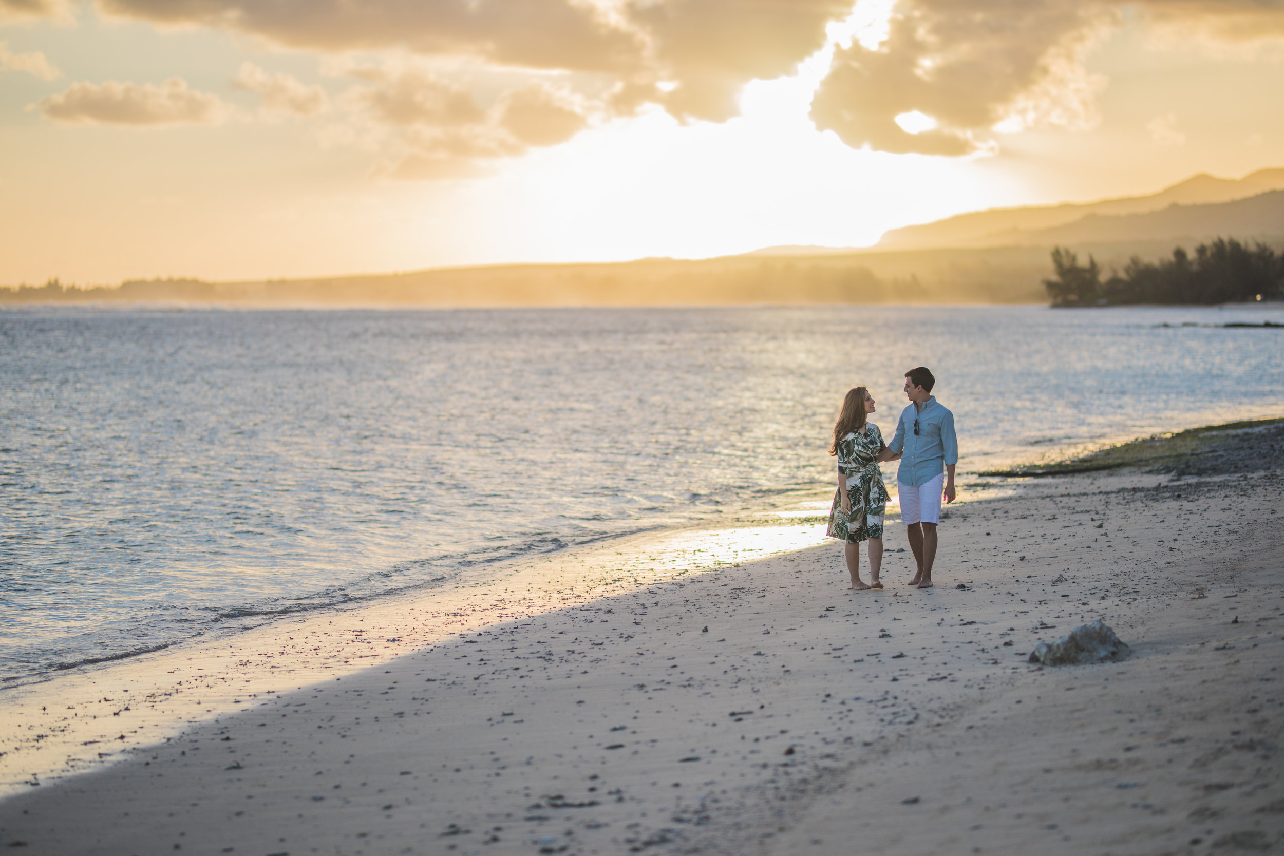 Couple walking on a beach with Sunset