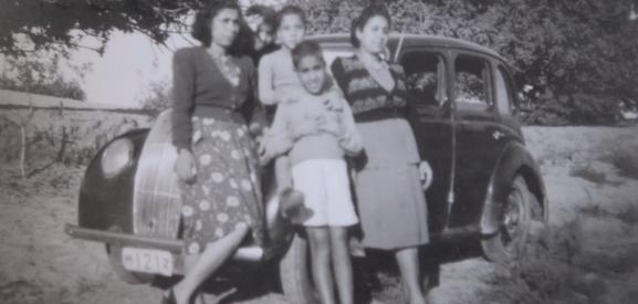 Women and Children standing proud near new car